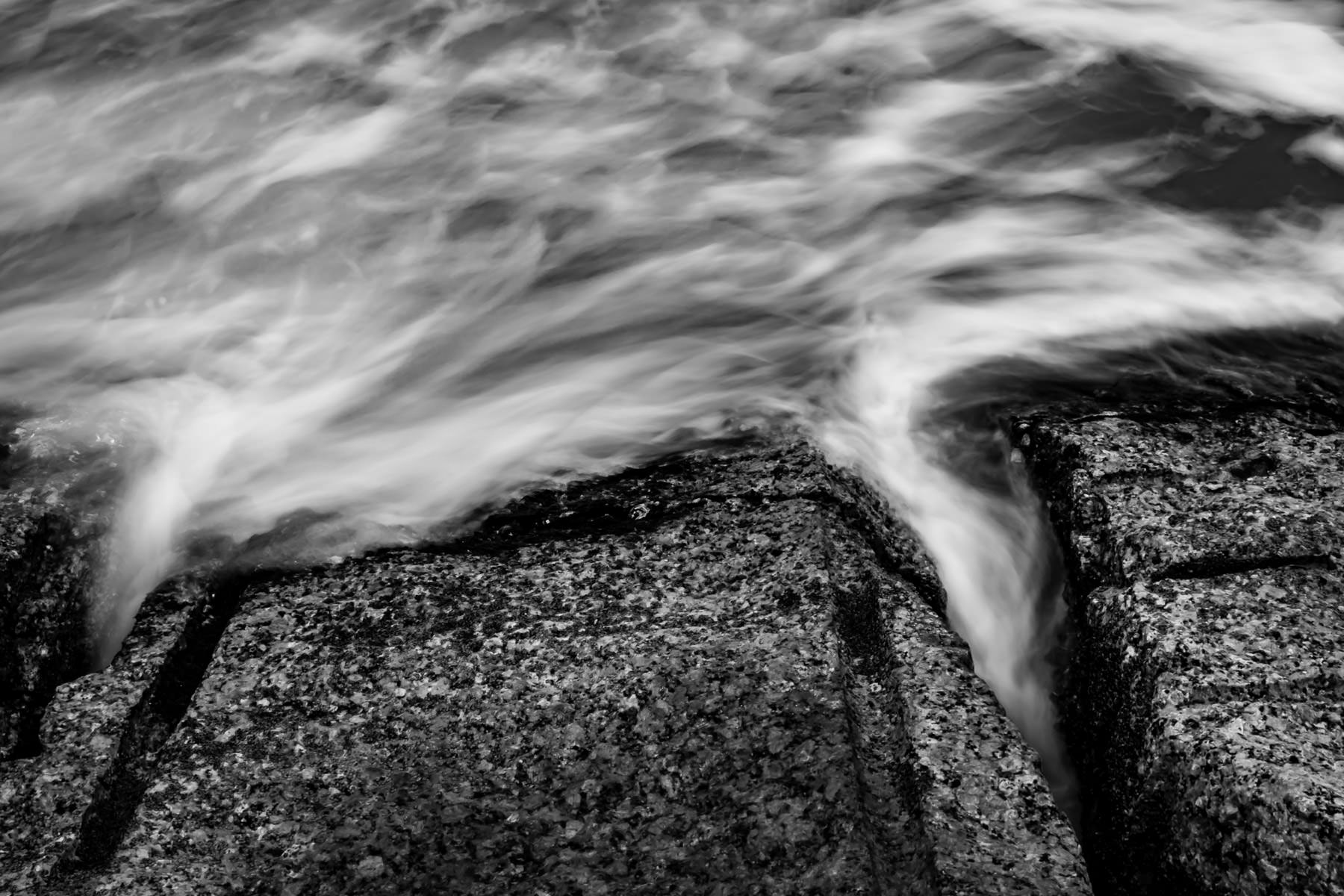 Flowing water in this long exposure shot resembles wisps of smoke curling around granite blocks making up a jetty or groyne on the Galveston, Texas, beach.