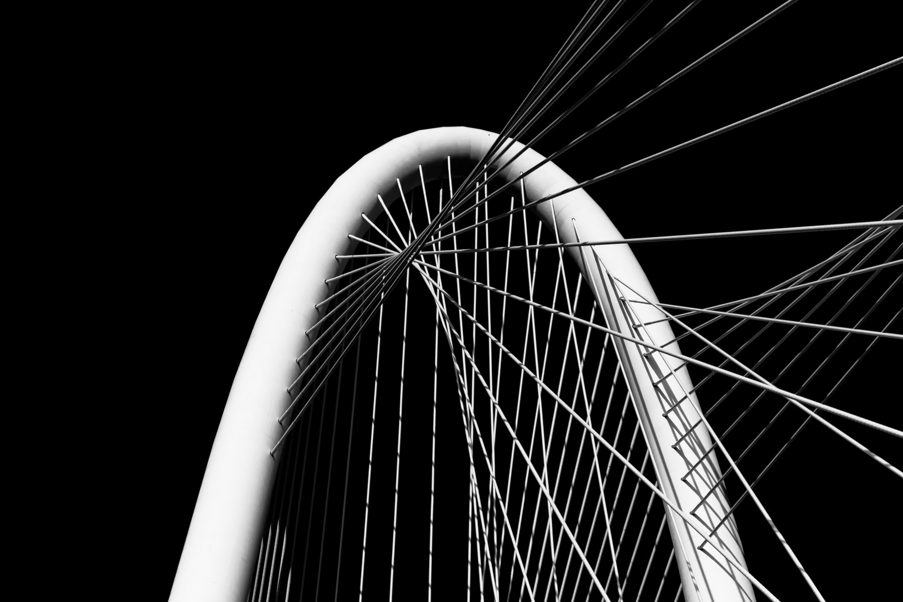 An abstract view of the arch and cables of the Santiago Calatrava-designed Margaret Hunt Hill Bridge in Dallas.