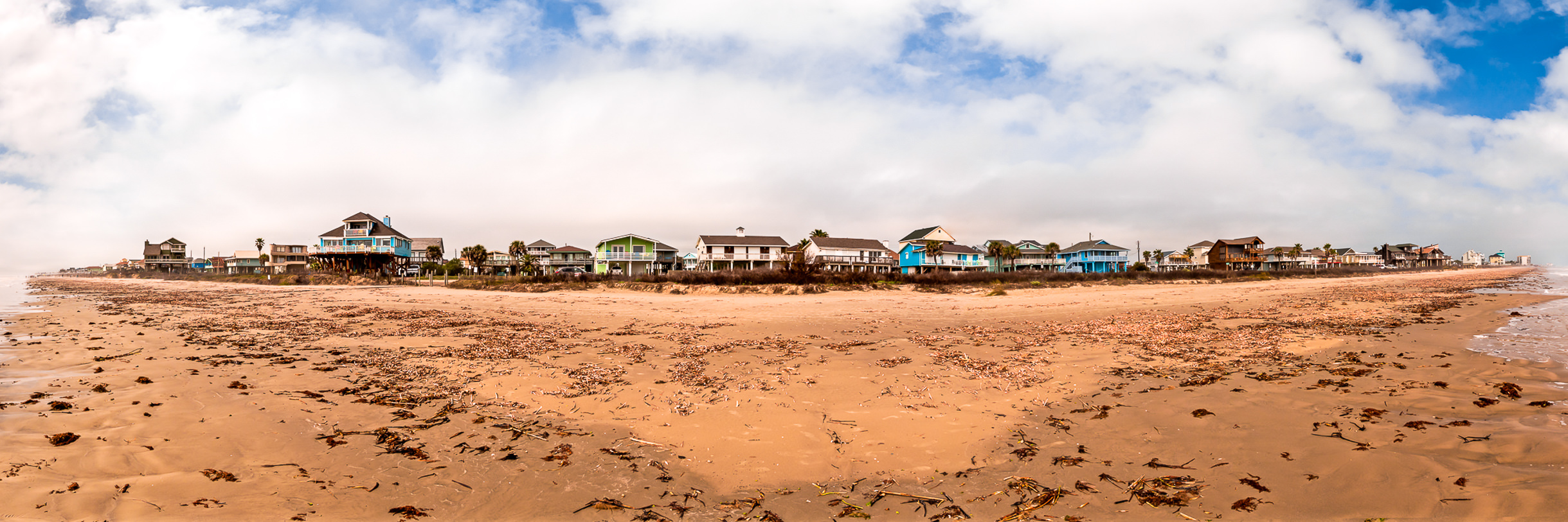 Beach houses line the seaweed-covered sandy beach at Galveston, Texas