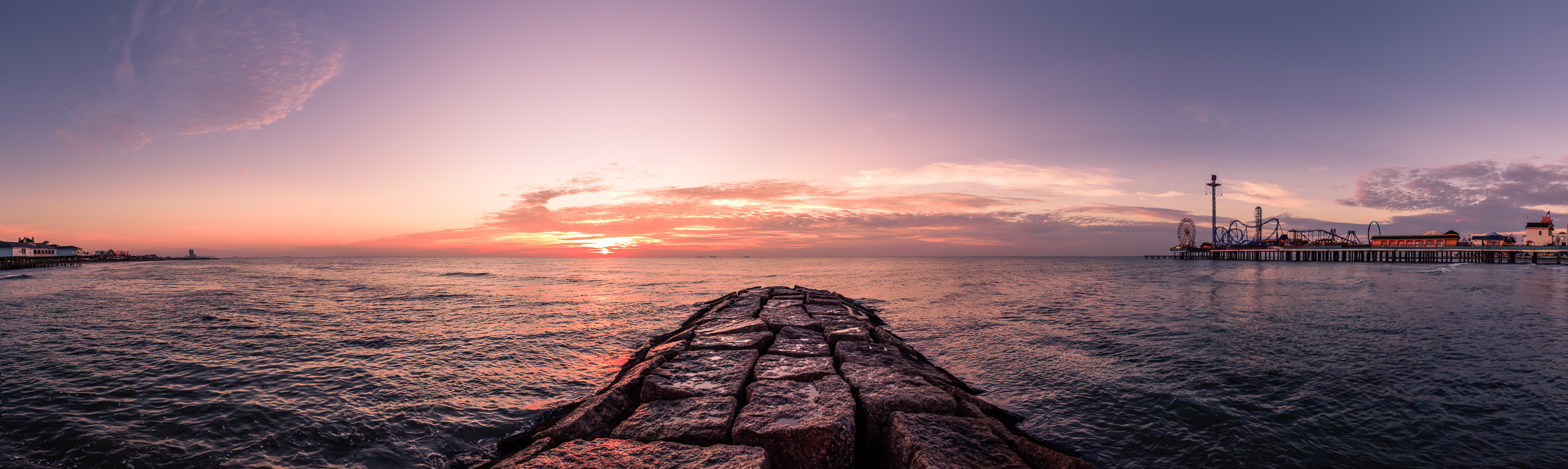 The sun rises over the Gulf of Mexico, as seen from a rock groyne on the Galveston, Texas, beach.