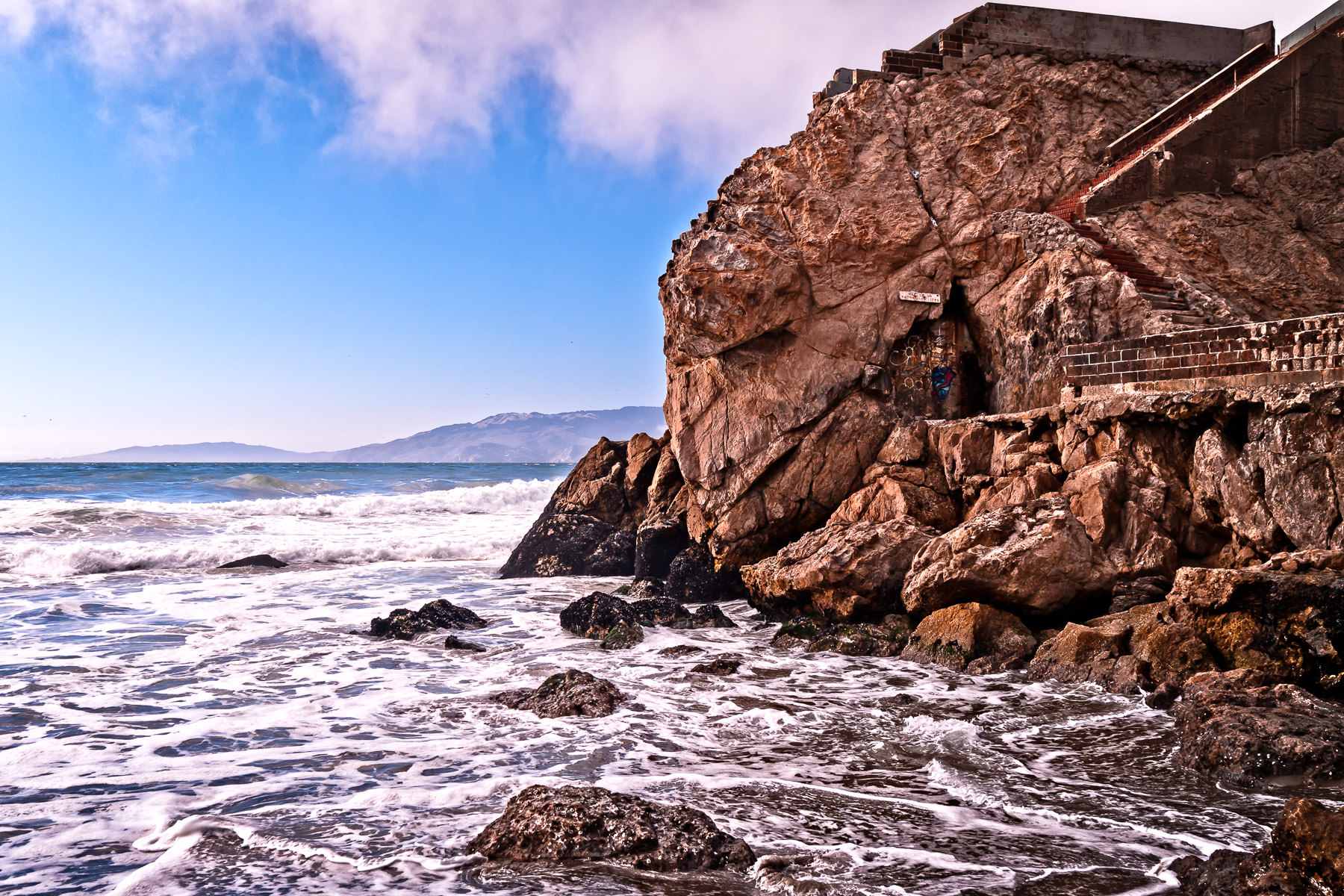 Part of the ruins of San Francisco's Sutro Baths sit perched above the roiling waves of the Pacific Ocean at Lands End.