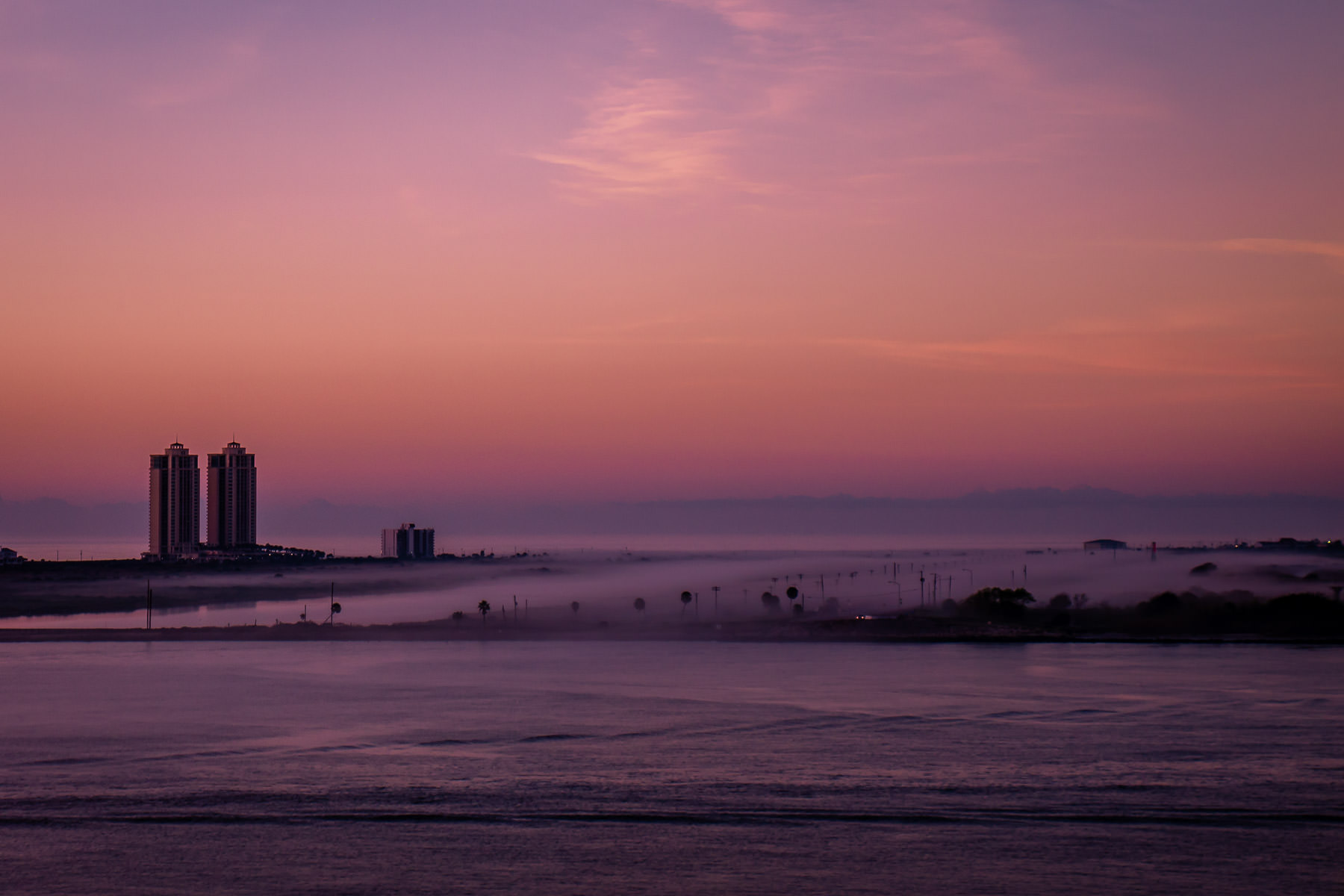 A low fog rolls over the north end of Galveston, Texas, as the first light of morning illuminates the island.