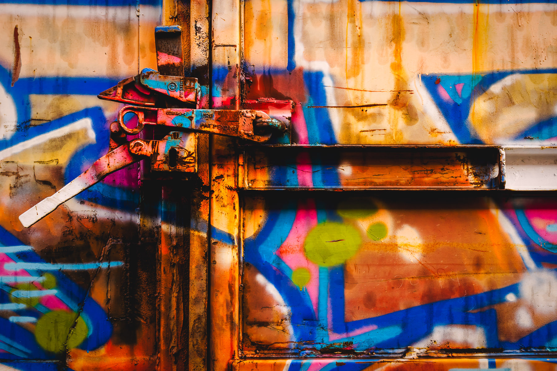 A graffiti-covered latch on a boxcar spotted in a Galveston, Texas, railyard.