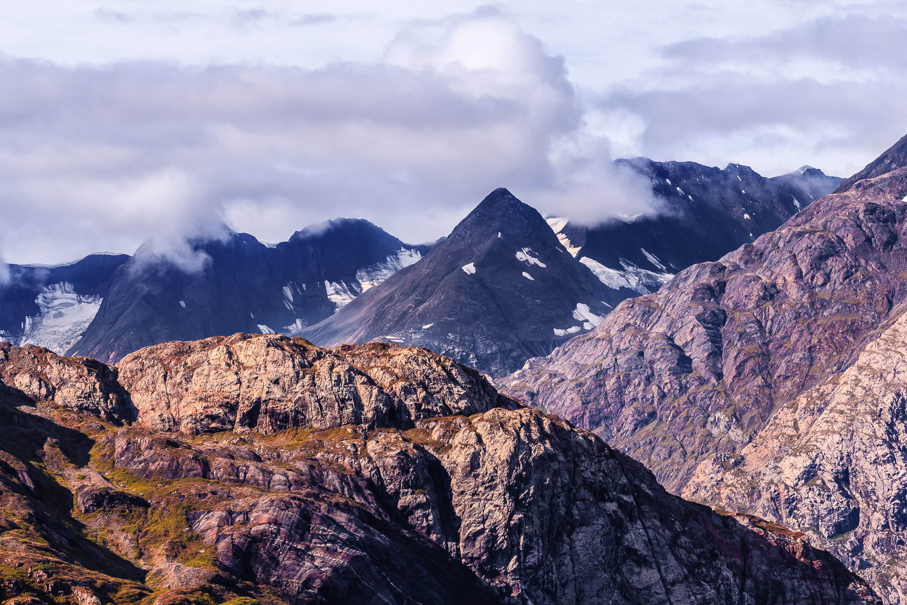 Rugged mountains rise into the clouds near Alaska's Glacier Bay National Park.