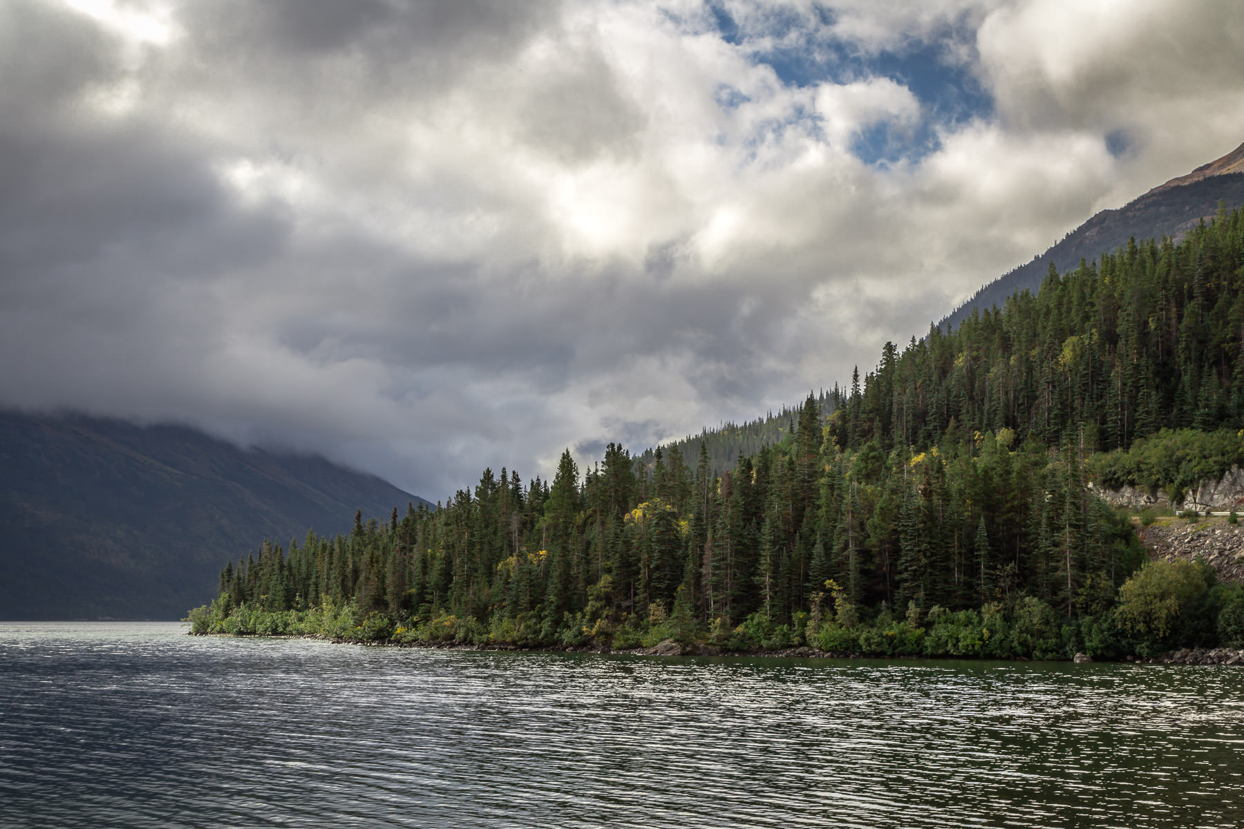 Low storm clouds roll in over the mountains surrounding British Columbia, Canada's Tutshi Lake.