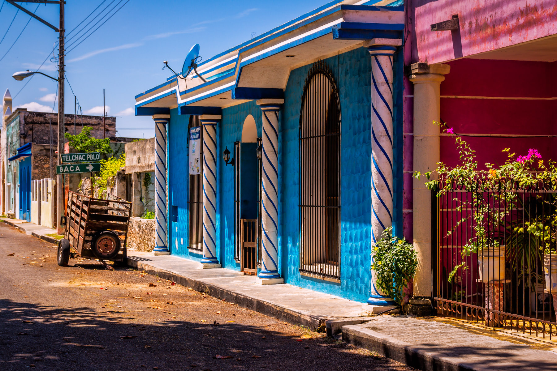 A wagon sits on the street amongst vivid buildings in Dzemul, Mexico.