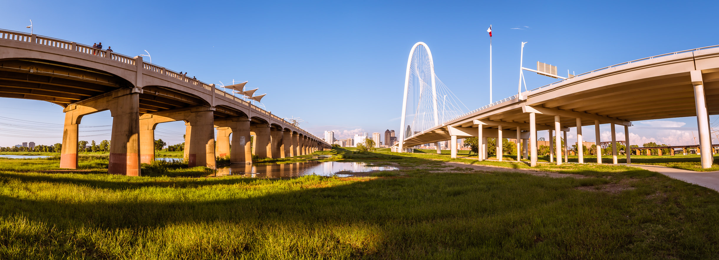 The Continental Avenue Viaduct and the Santiago Calatrava-designed Margaret Hunt Hill Bridge stretch over the Trinity River towards Downtown Dallas.