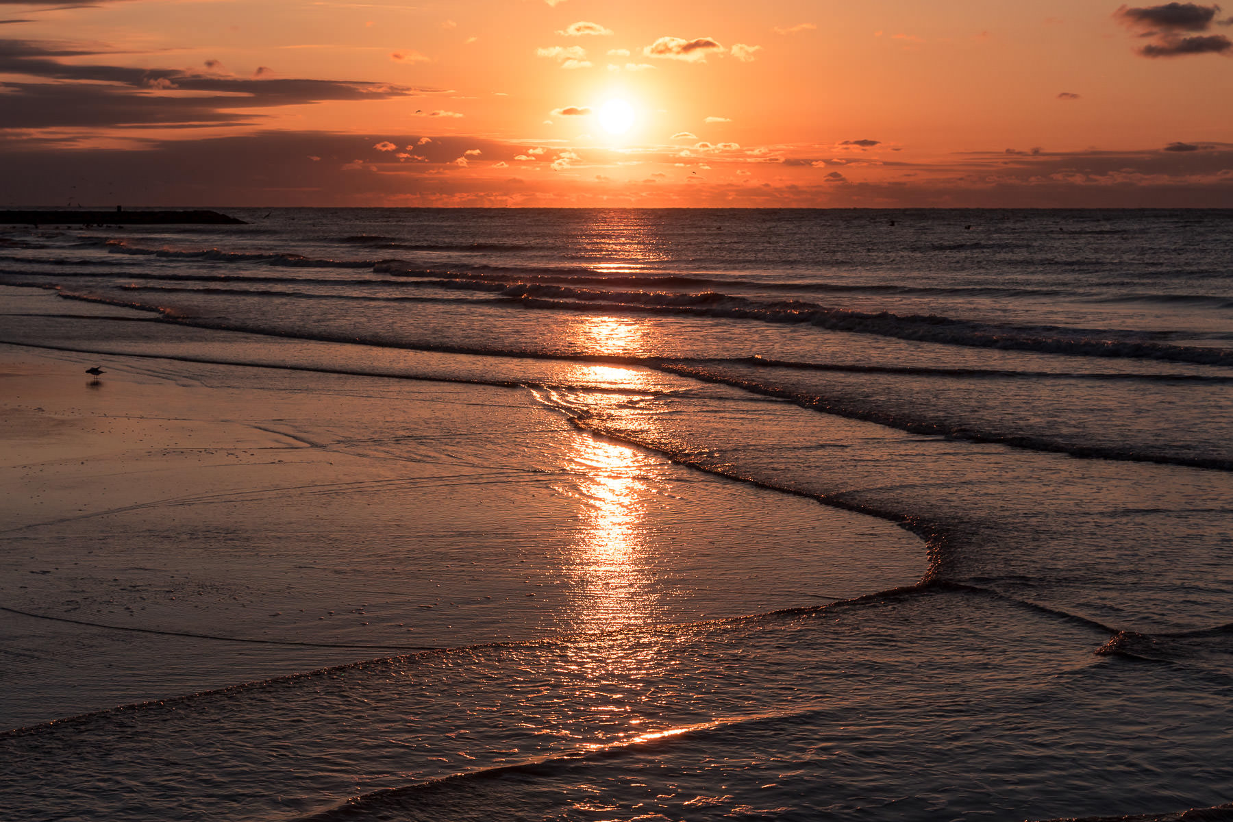 The sun rises over the beach at Galveston, Texas.