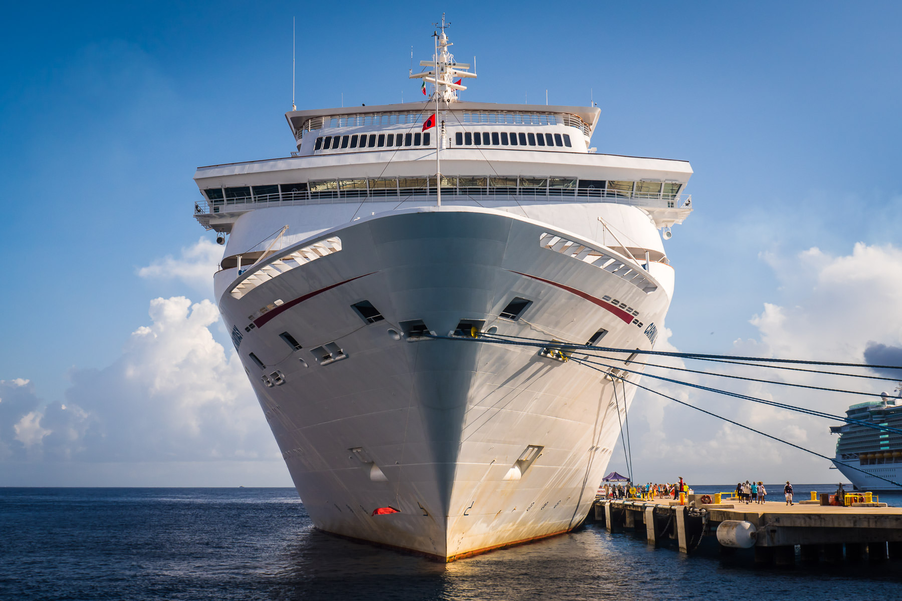 The bow of the cruise shipCarnival Fantasy looms over the adjacent pier at Cozumel, Mexico.