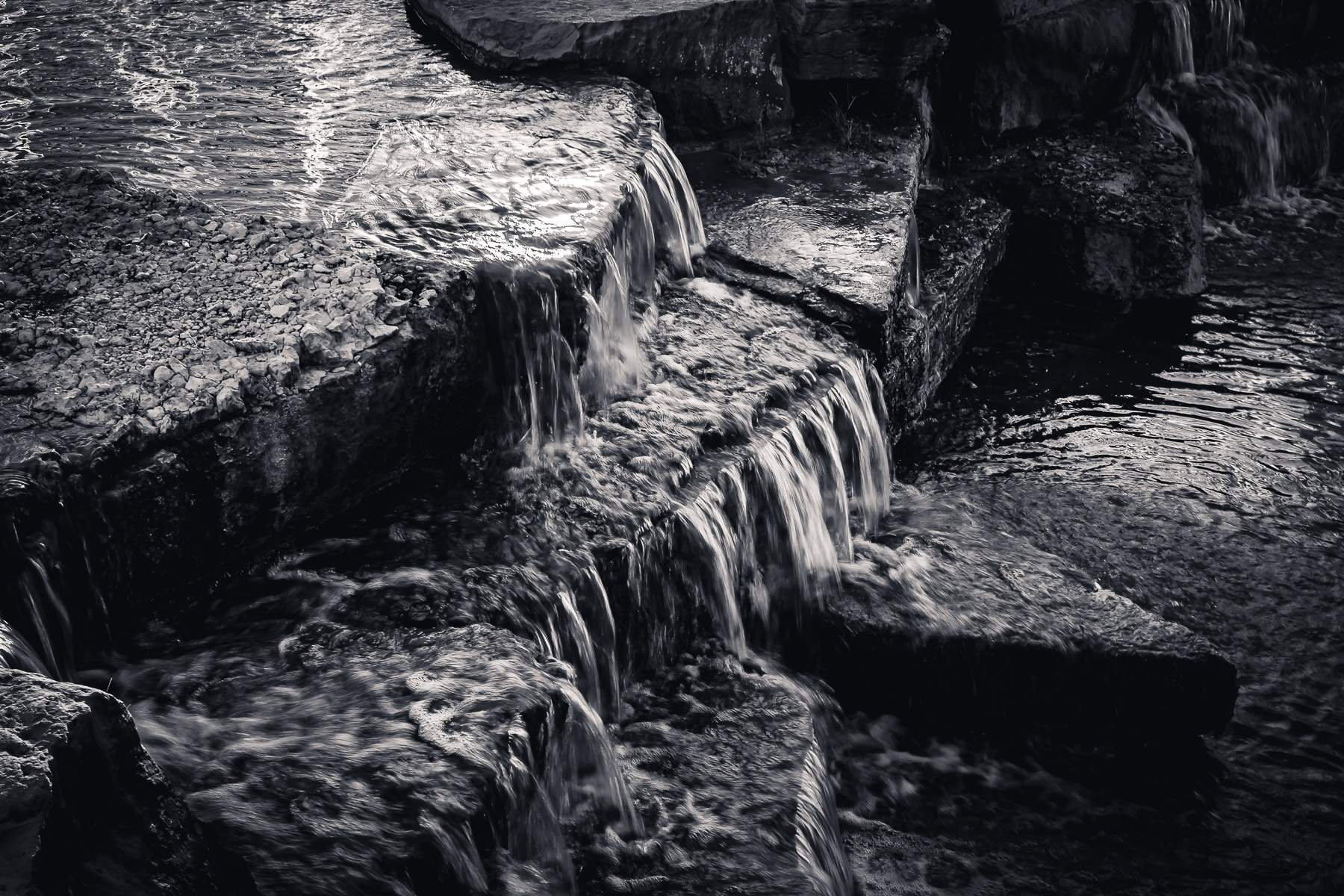 Water flows over rocks at Hall Office Park in Frisco, Texas.
