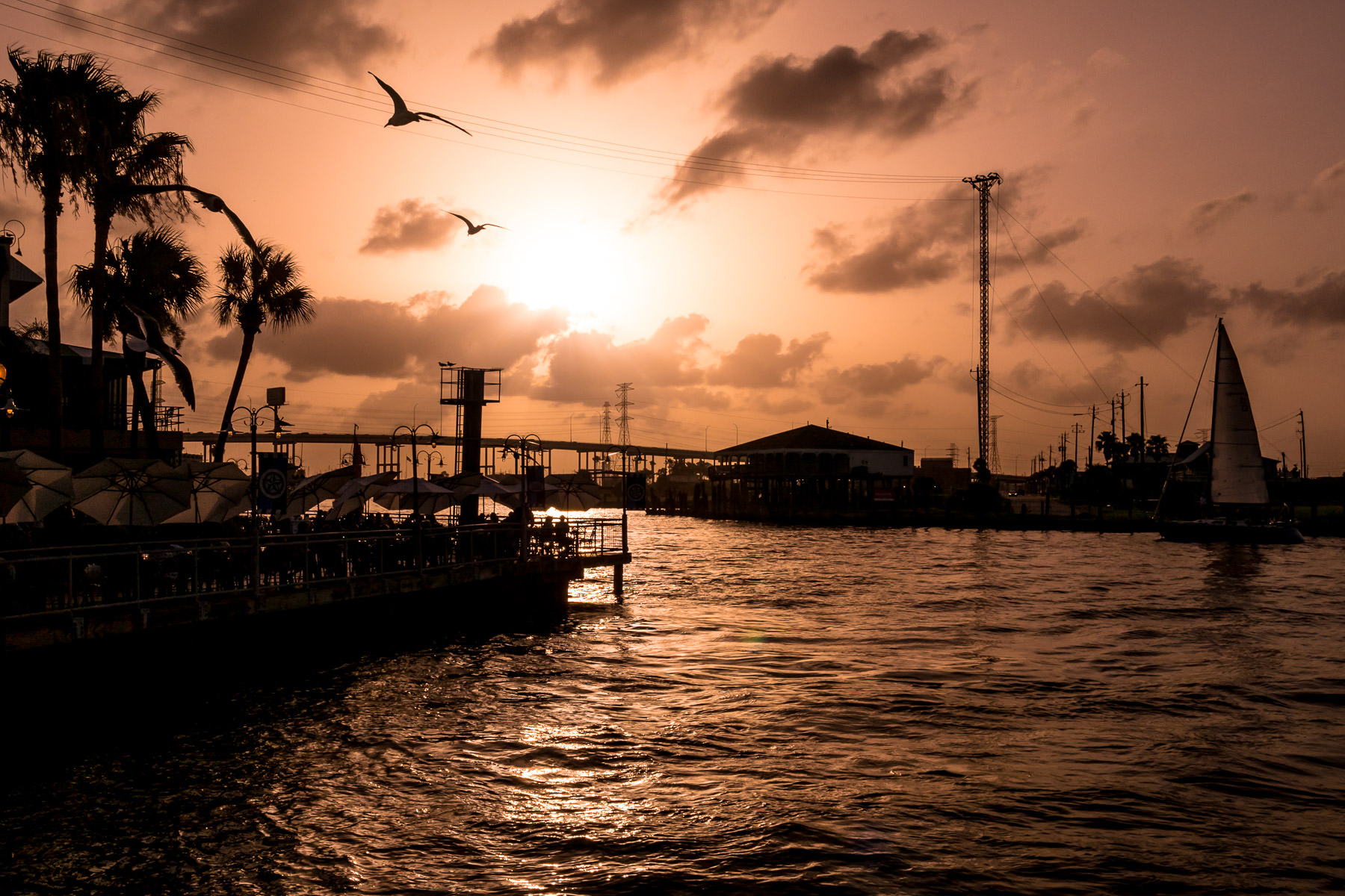 Birds fly by as the sun sets on the Kemah Boardwalk in Kemah, Texas.