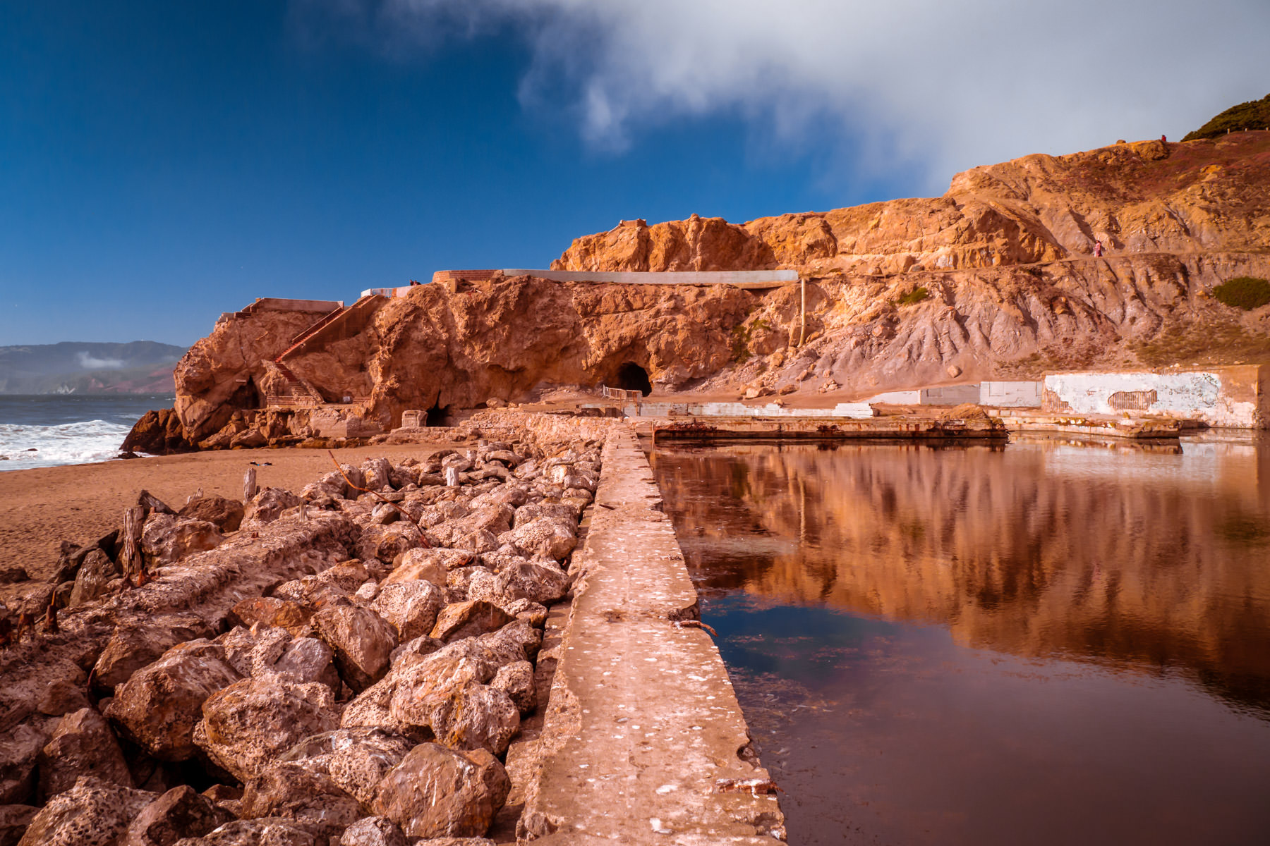 The bluffs of San Francisco's Lands End are reflected in a pool amongst the ruins of Sutro Baths.