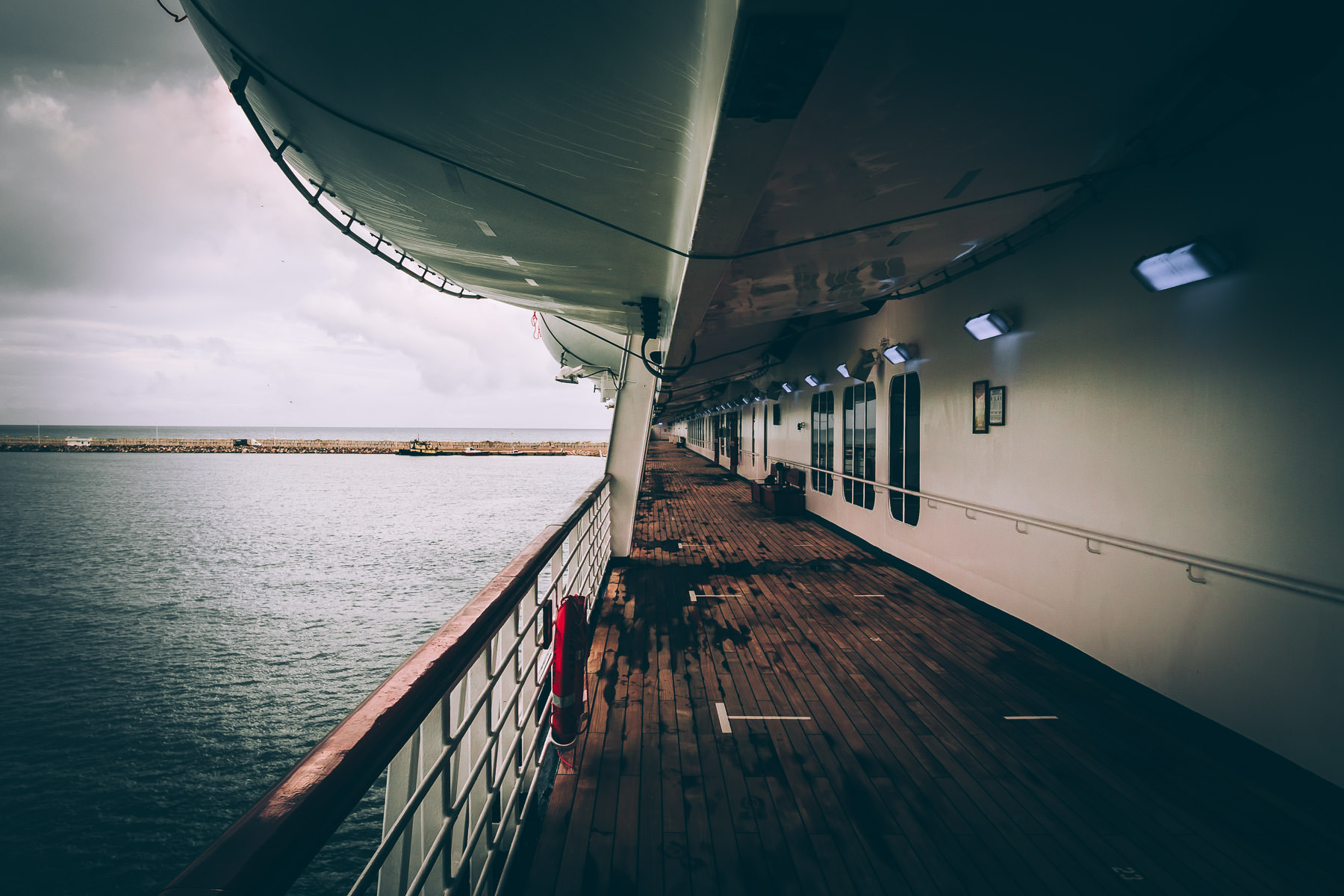 The port side of deck 3 of the cruise ship Carnival Triumph while docked in Progreso, Mexico, on an overcast day.