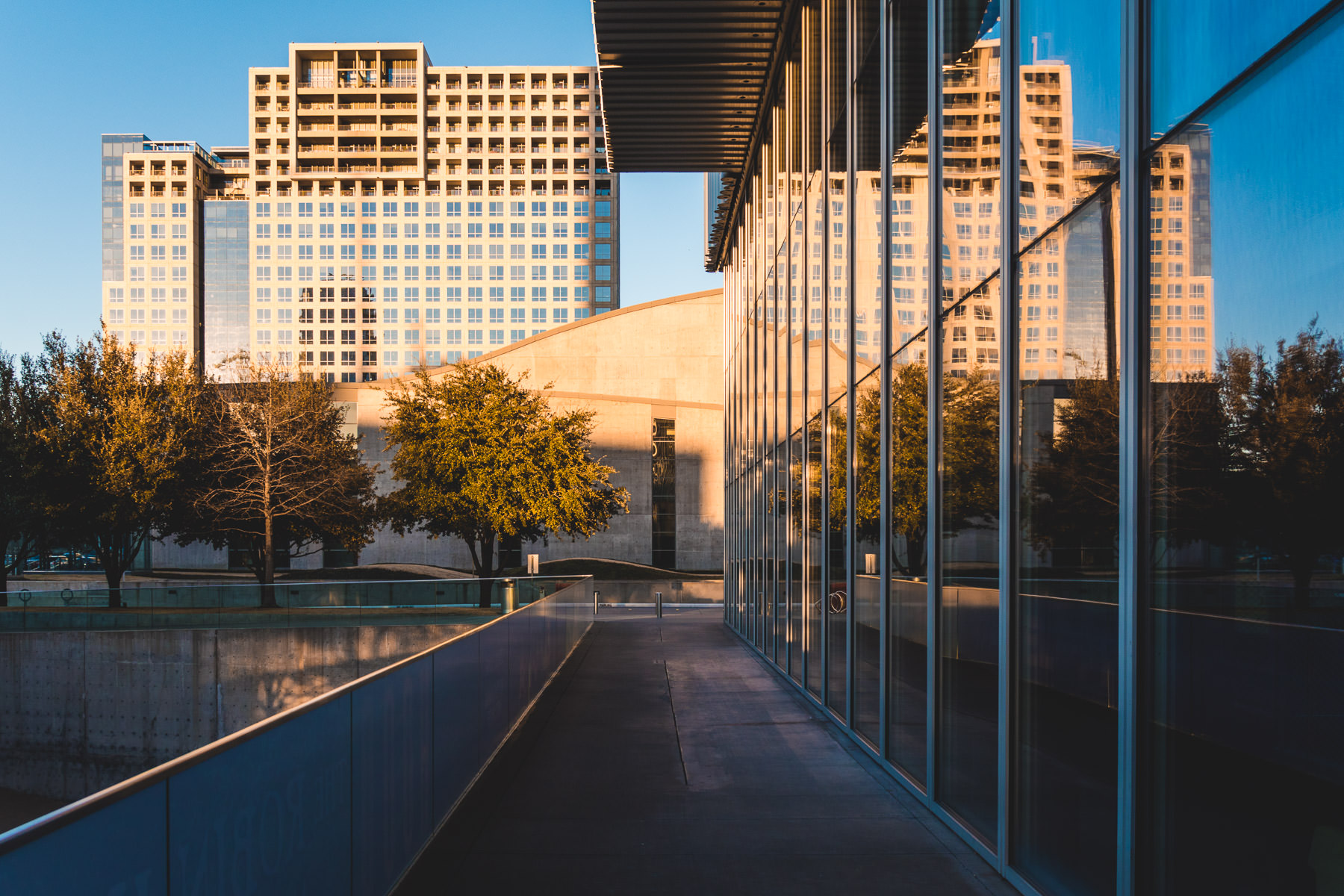 The Dallas Arts District's One Arts Plaza is reflected in the glass facade of the adjacent Wyly Theatre.
