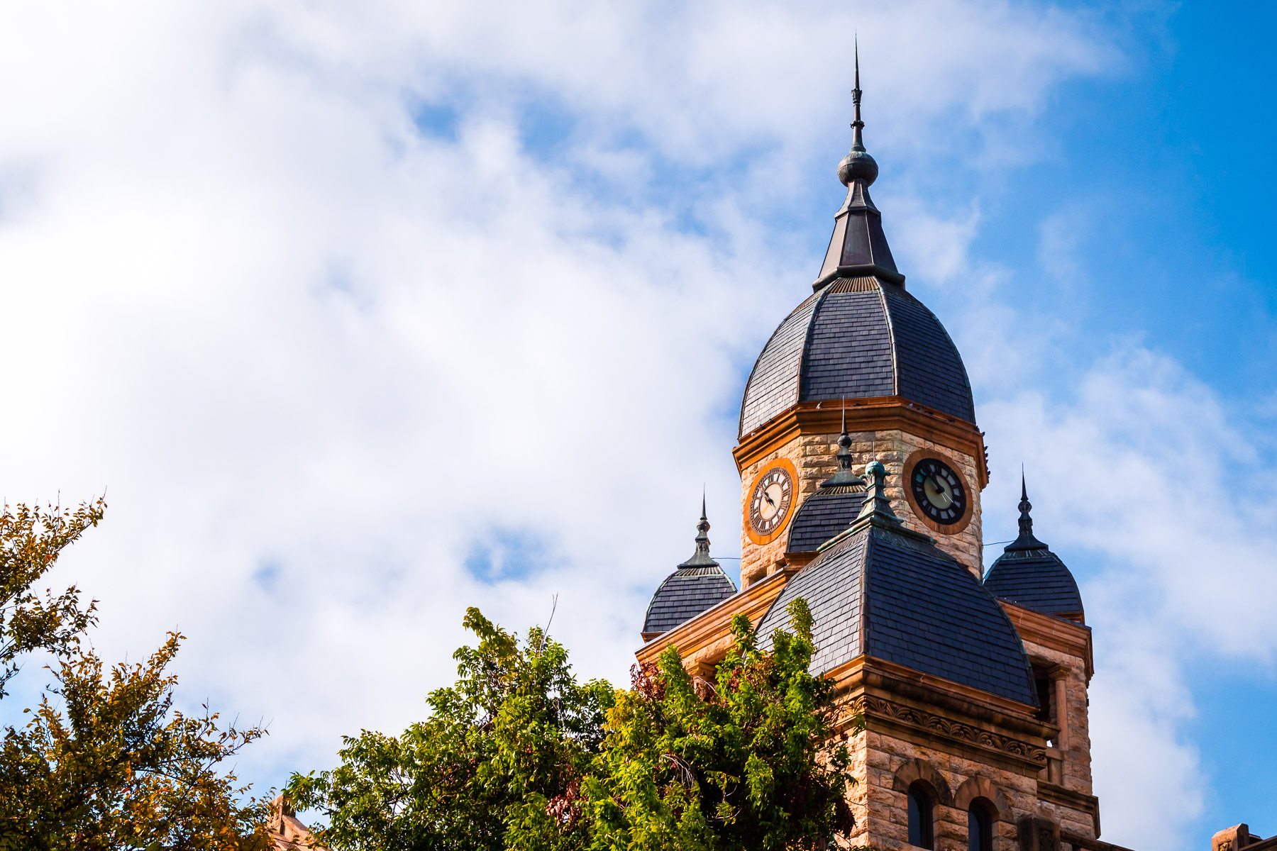 The clock tower at Denton County Courthouse rises into the sky over Denton, Texas.