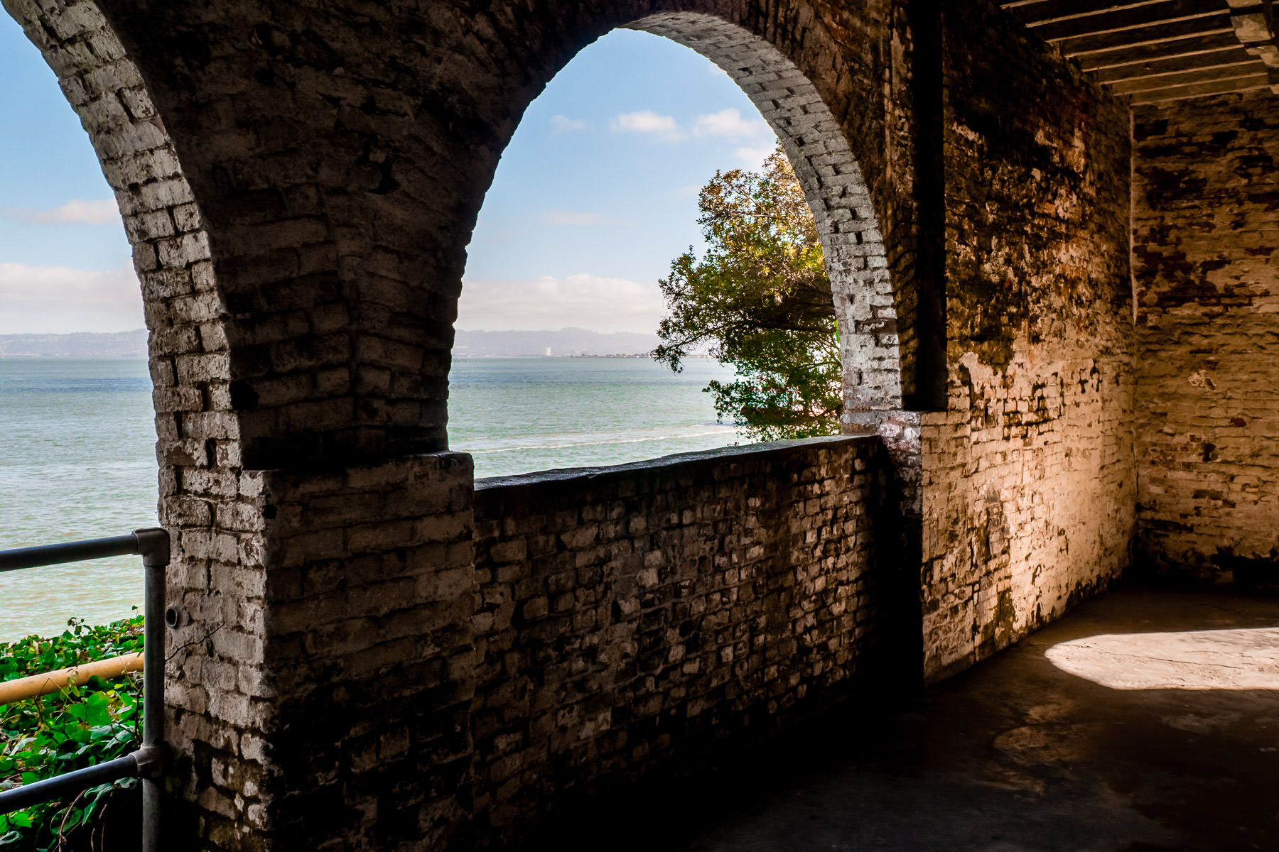 A brick archway offers a view of San Francisco Bay at the historic Alcatraz Federal Penitentiary.