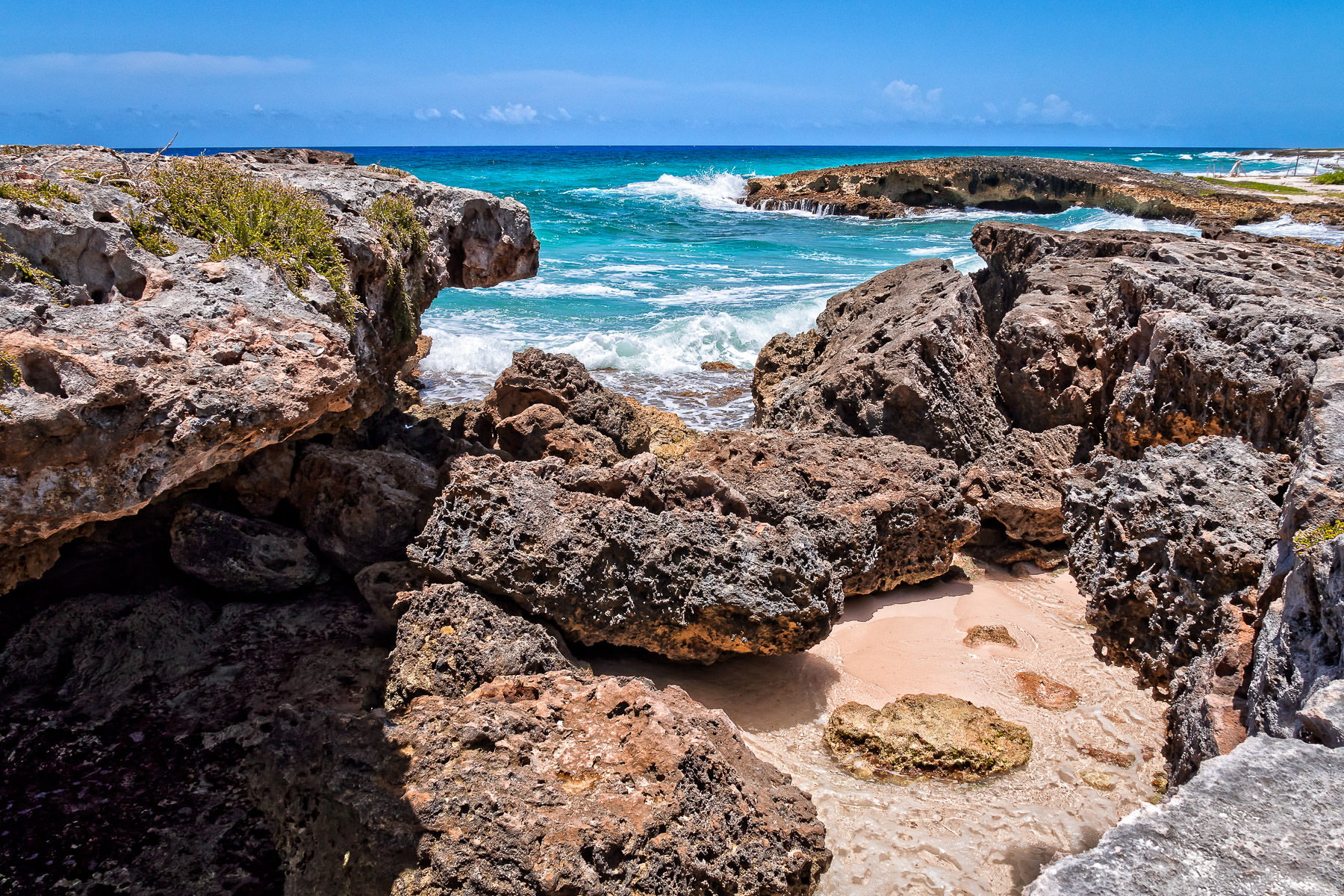 Surf swirls around the rocky shore at El Mirador, Cozumel, Mexico.