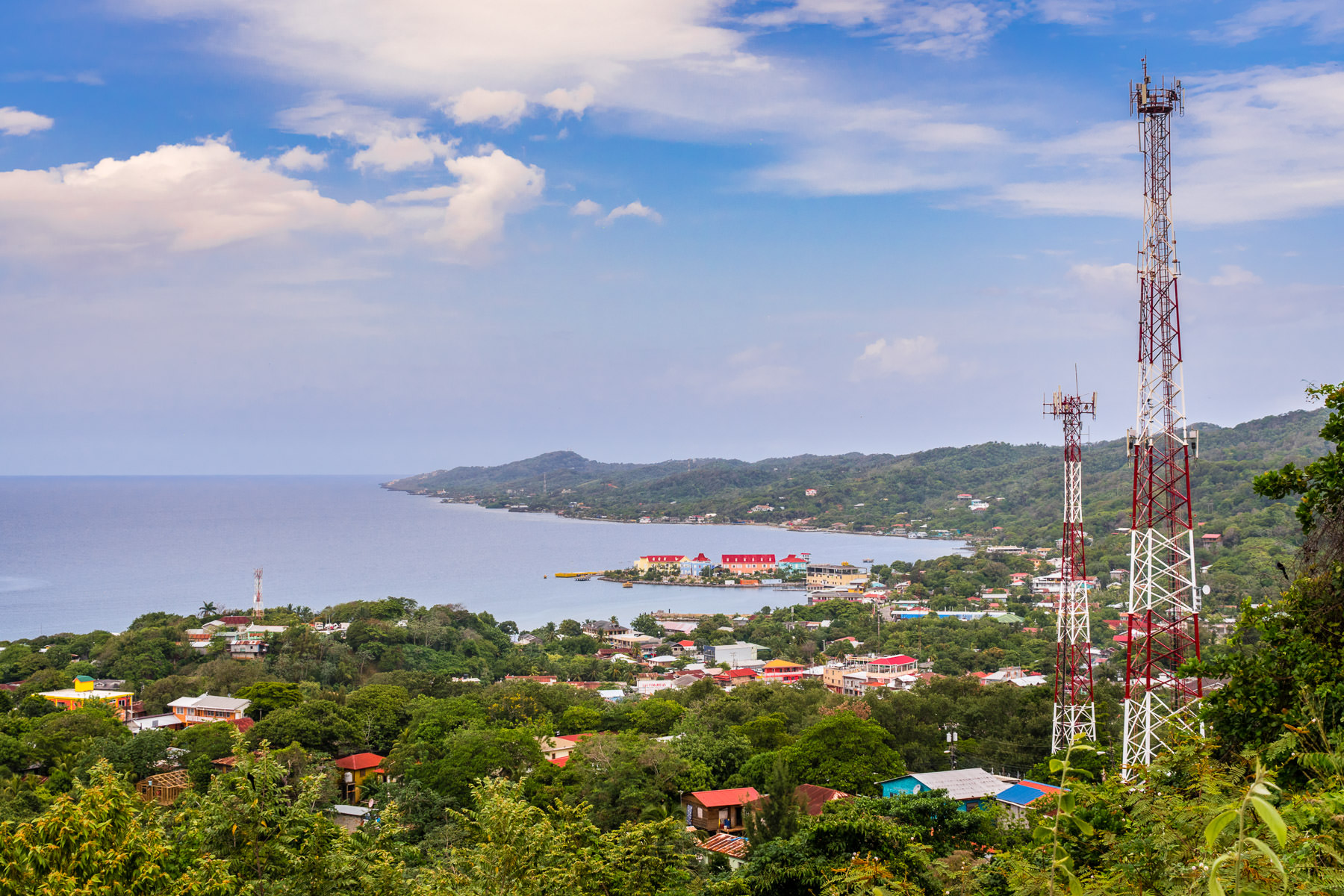 Cell towers rise over the lush tropical landscape of the island of Roatan, Honduras.