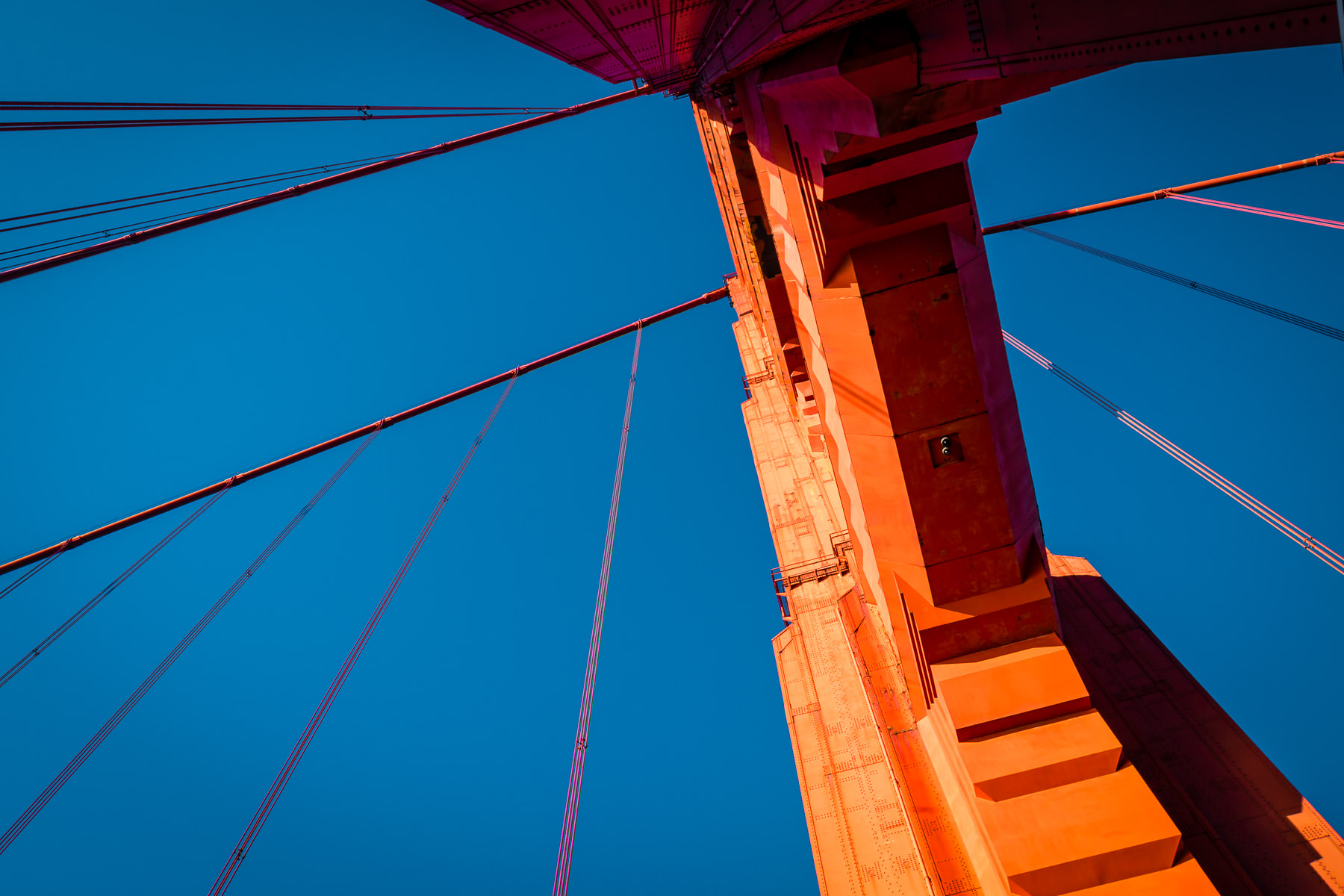 The 746-foot-tall south tower of the Golden Gate Bridge rises into the clear sky over San Francisco Bay.