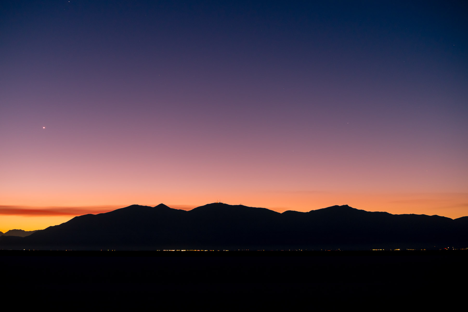 The first light of dawn crests the Wasatch Front as lights of Salt Lake City glimmer in the distance, as seen from the Great Salt Lake's Stansbury Island.