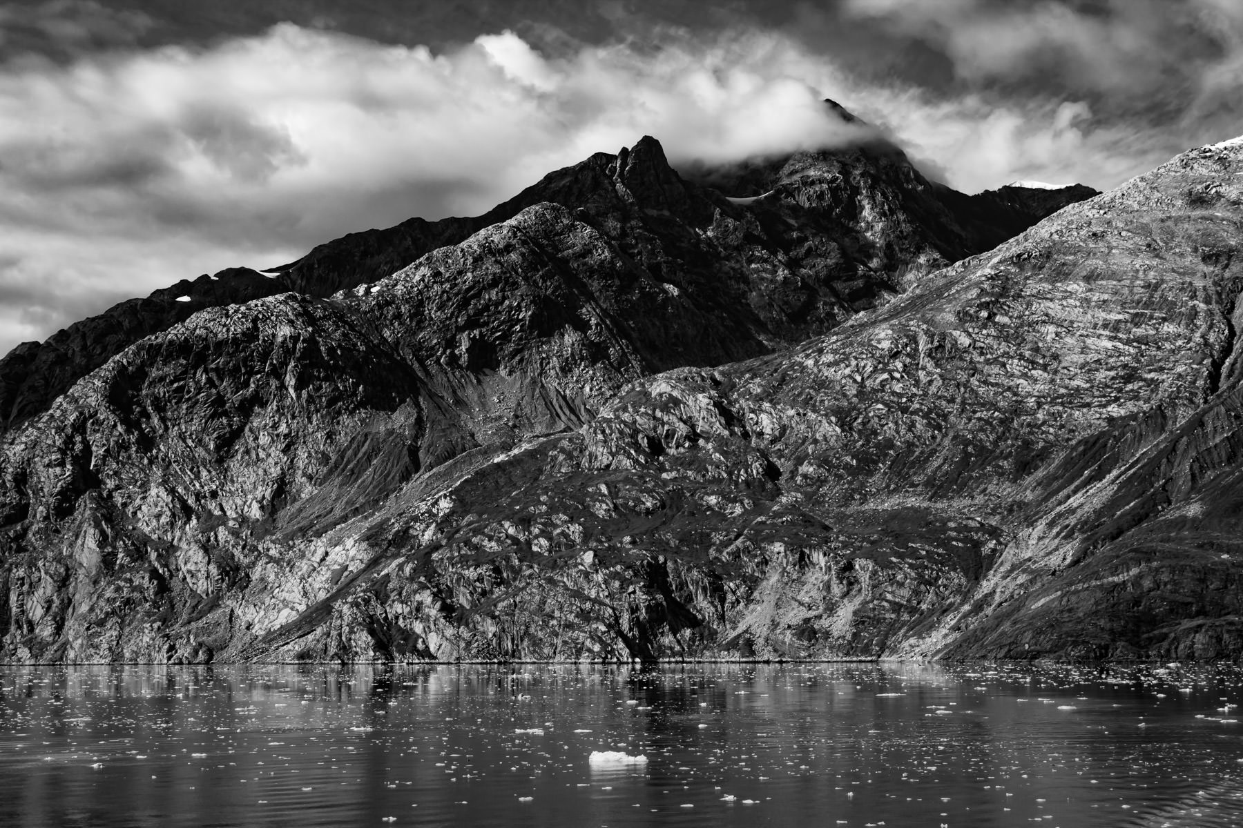 Rugged mountains along the shore of Alaska's Glacier Bay reach into the clouds.