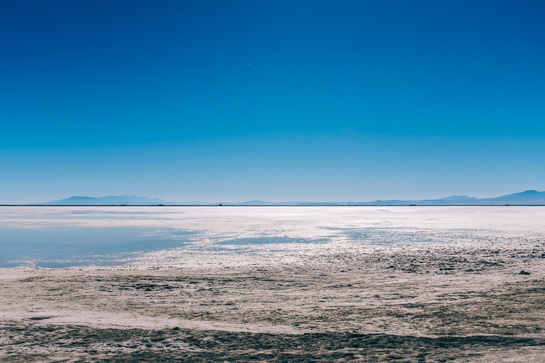Utah's Bonneville Salt Flats stretch to the horizon as traffic transits Interstate 80 in the distance.