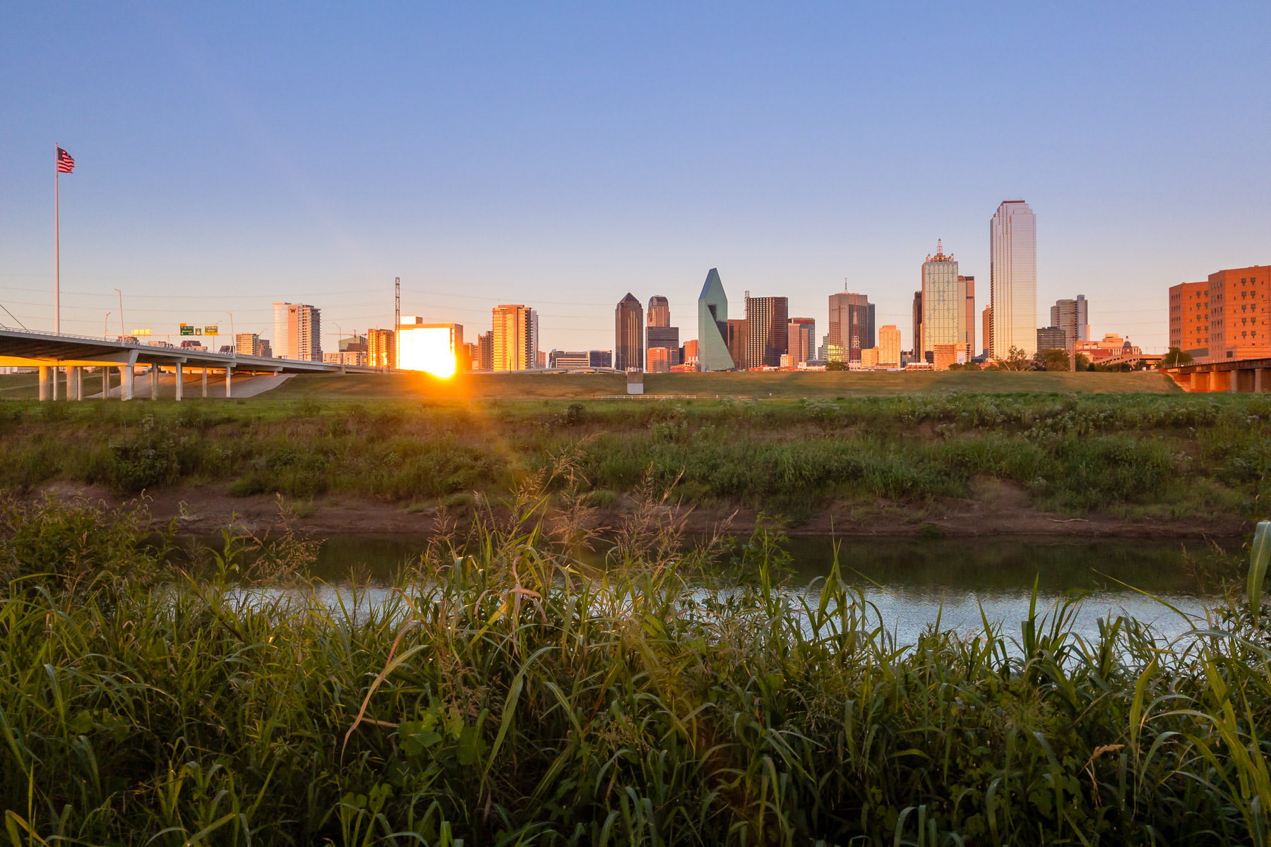 The late-evening sun glints off the buildings of Downtown Dallas.