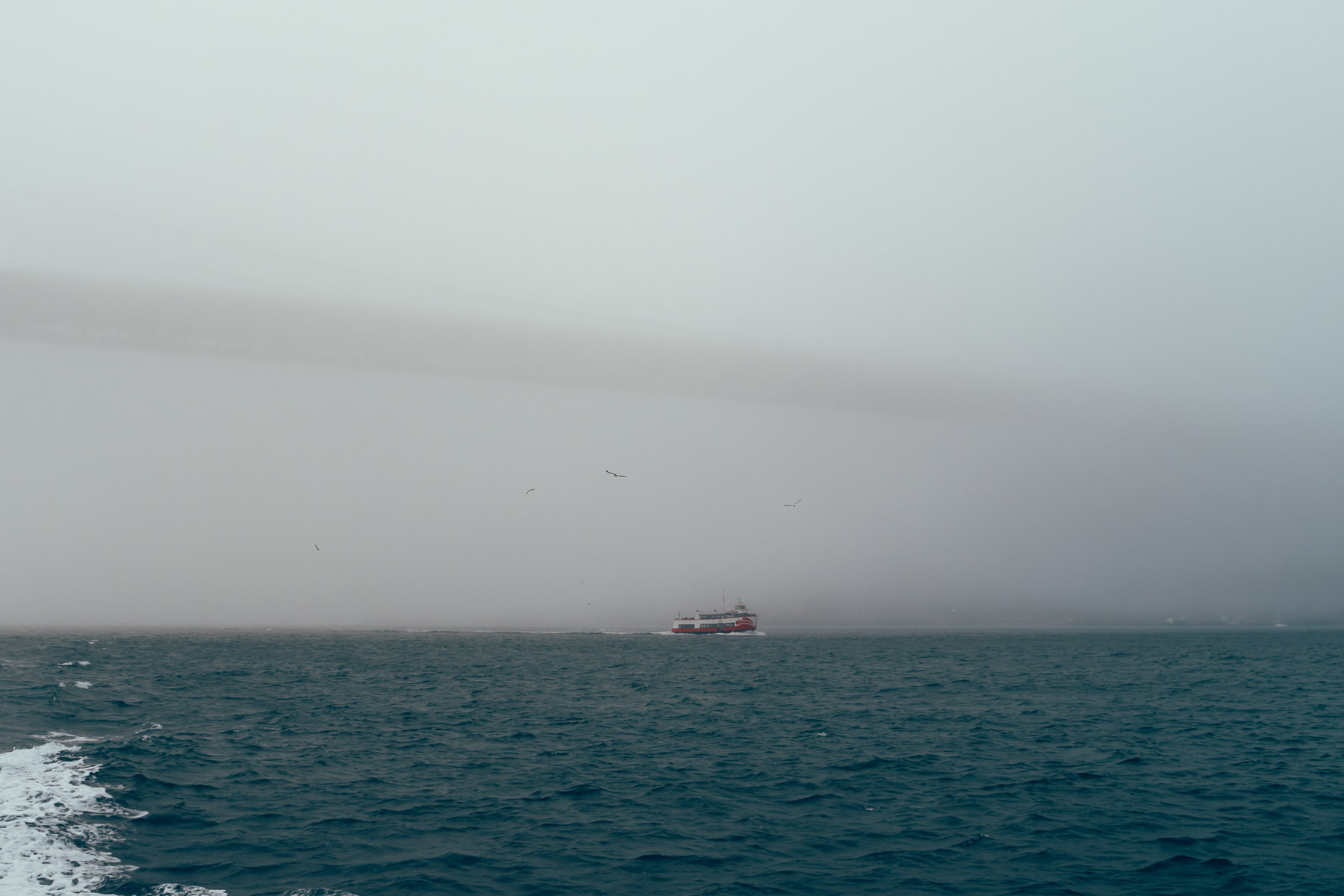 A Red and White Fleet boat carrying sightseers sails under the ominous fog-bound Golden Gate Bridge in San Francisco Bay.