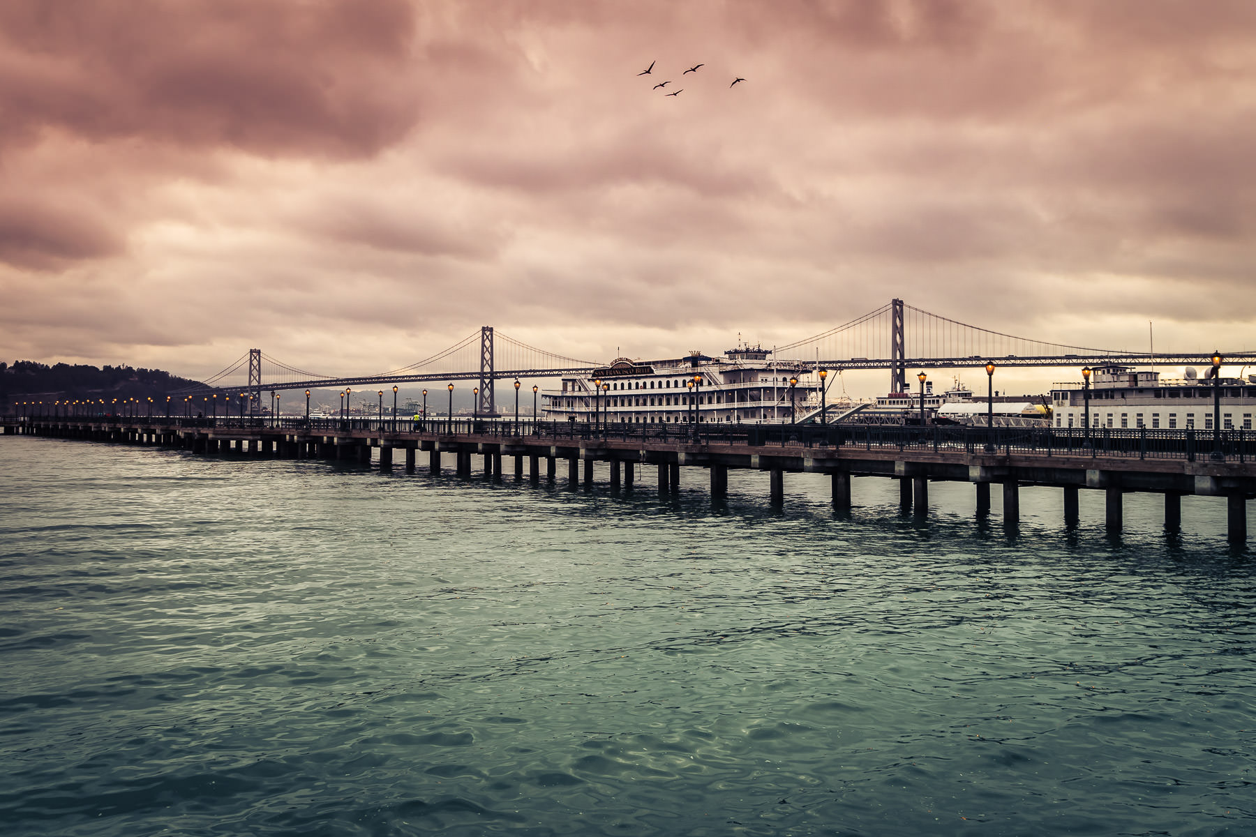 San Francisco's Pier 7 stretches out into San Francisco Bay, overshadowed by the nearby Bay Bridge.