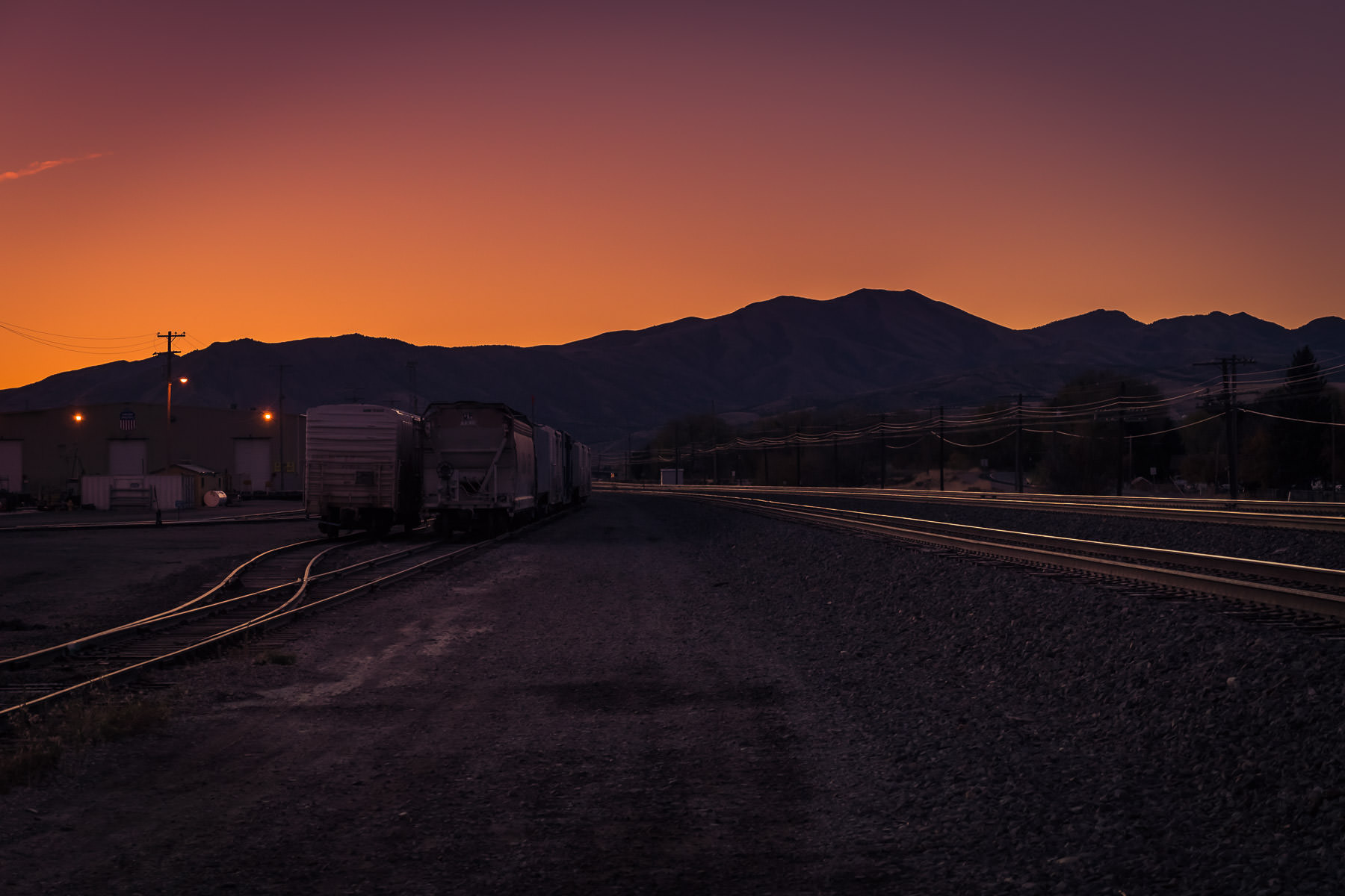 The sun rises beyond the mountains near a rail yard on the outskirts of Pocatello, Idaho.