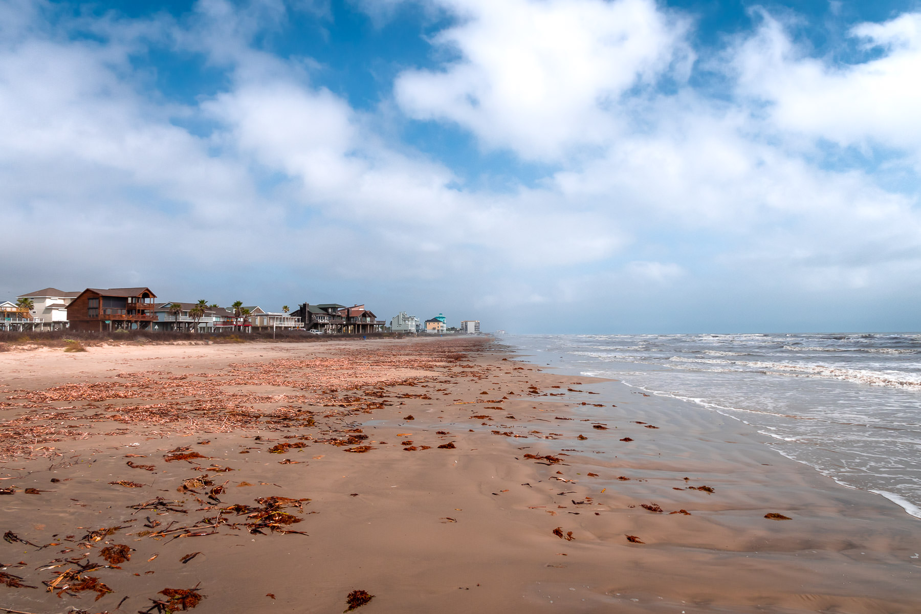 Clouds roll over a seaweed-covered beach at Galveston, Texas.