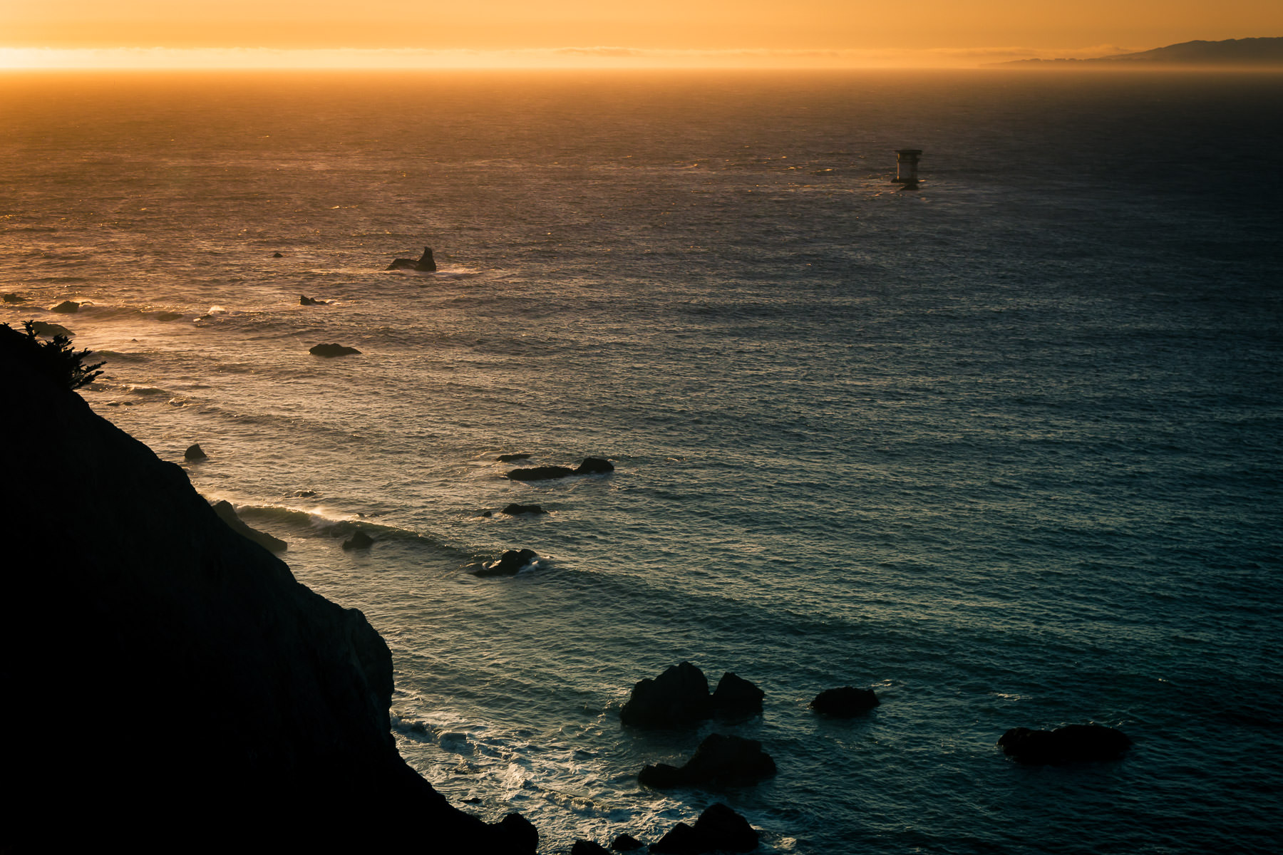 The sun sets on the Mile Rocks Light and the mouth of San Francisco Bay at Lands End, California.