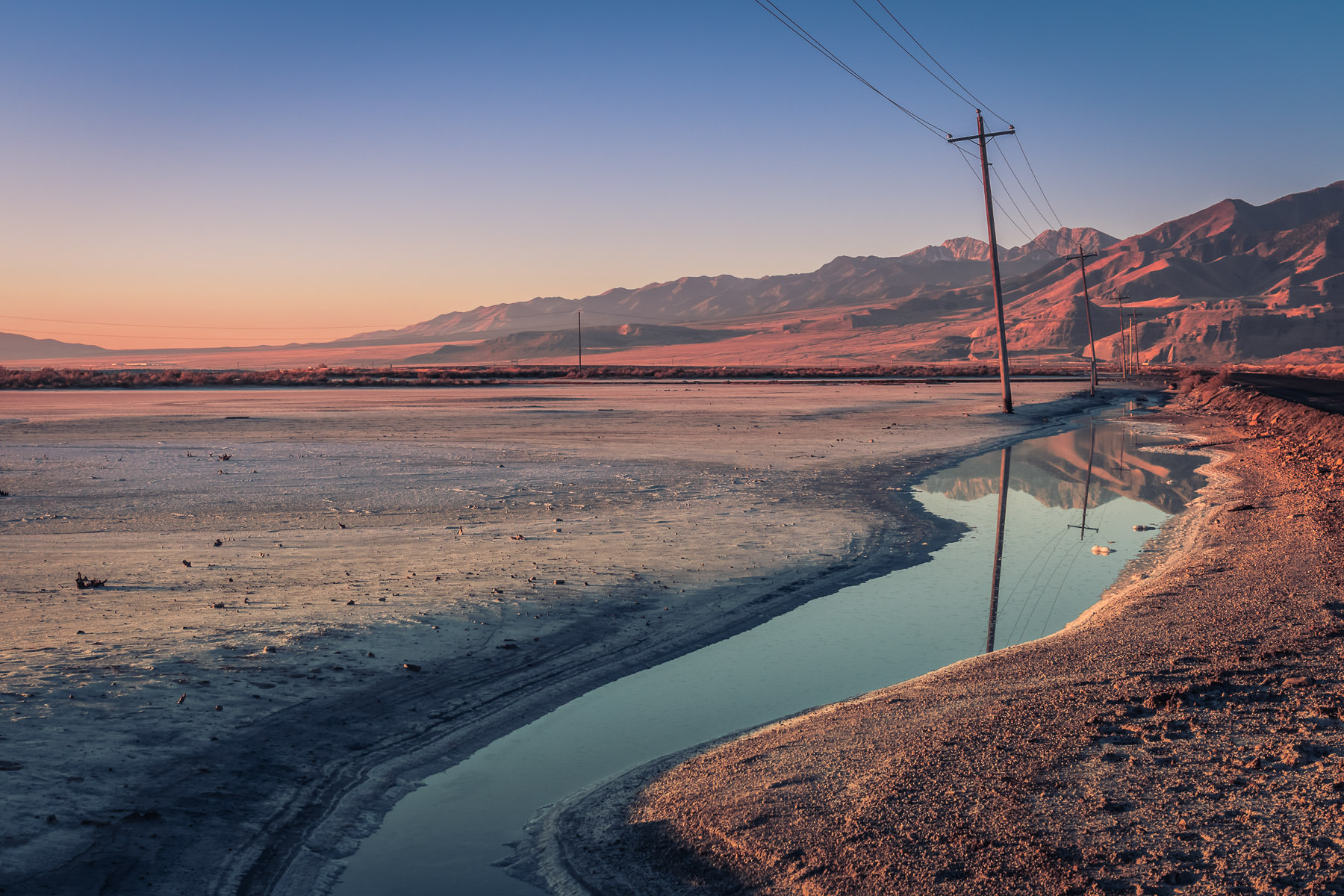 Power lines stretch along the road to Utah's Stansbury Island along the shore of the Great Salt Lake.