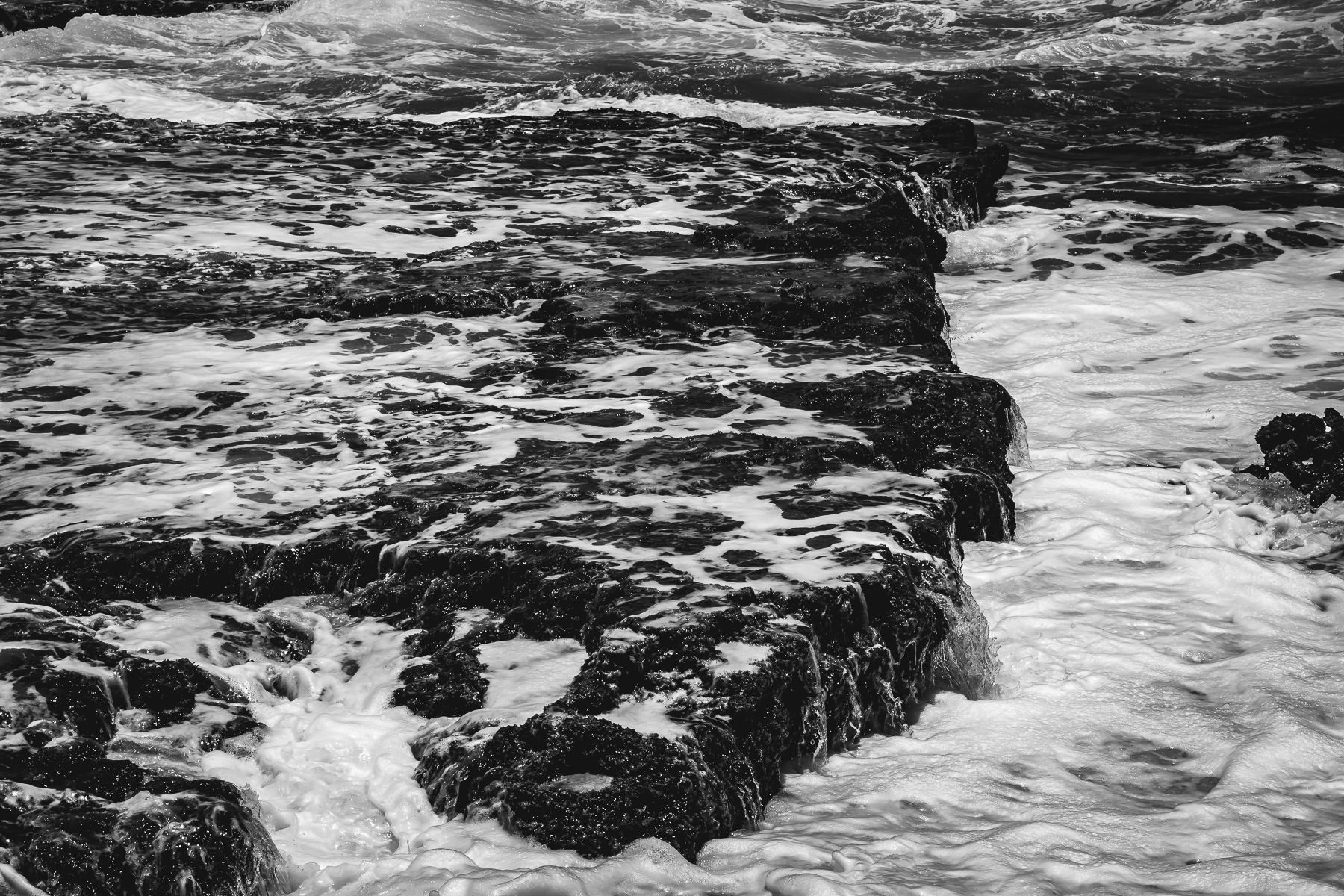 Atlantic Ocean waves drain over the rocky shoreline at El Mirador, Cozumel, Mexico.