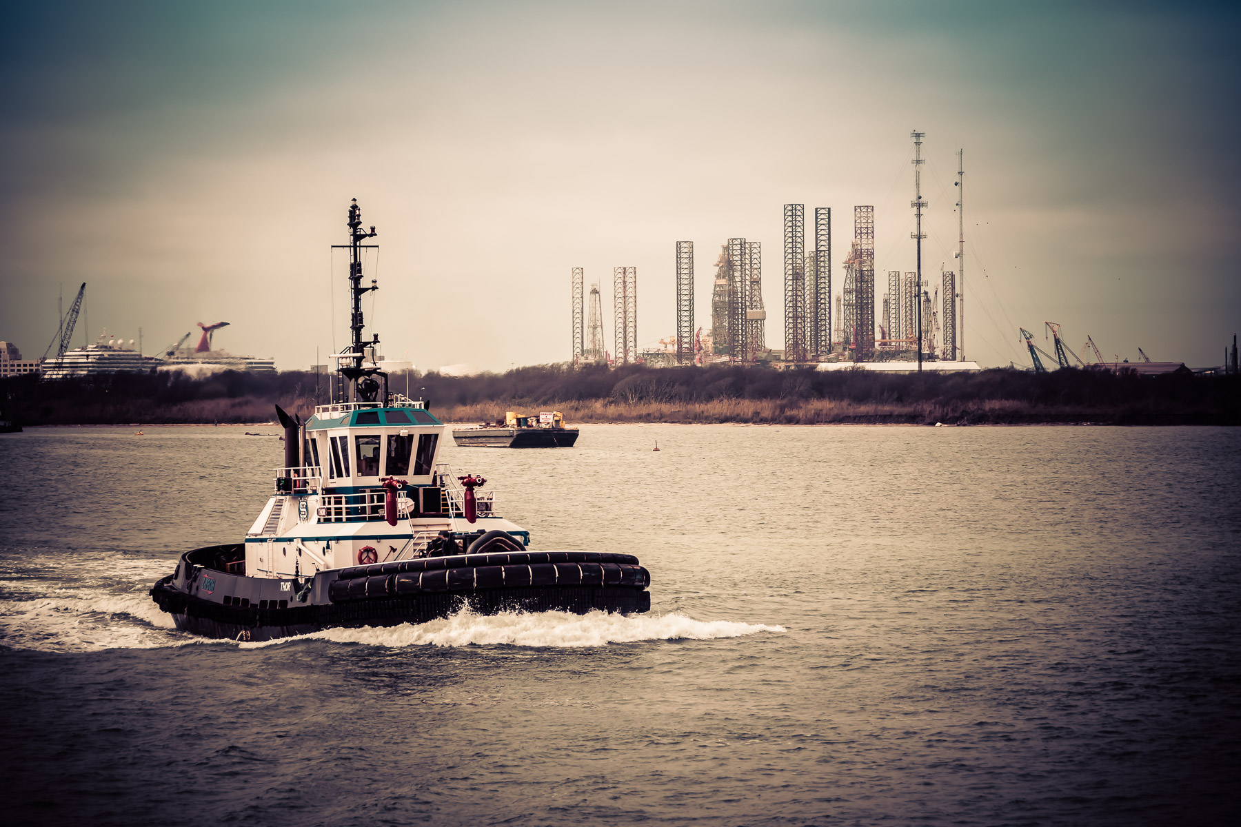 A tugboat transits the entrance to Galveston Bay at the northeast end of Galveston Island, Texas.