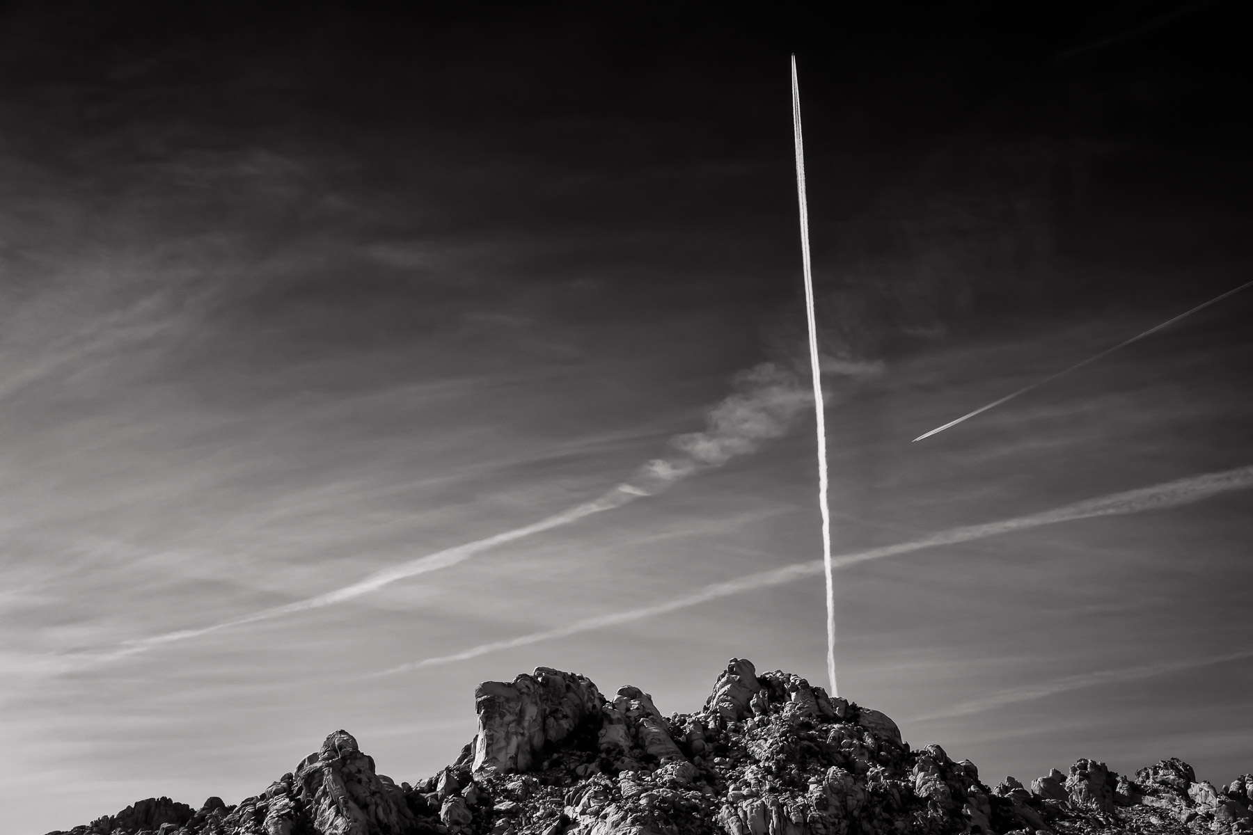 A high-flying jet leaves a contrail in the desert sky over the Mojave National Preserve, California.