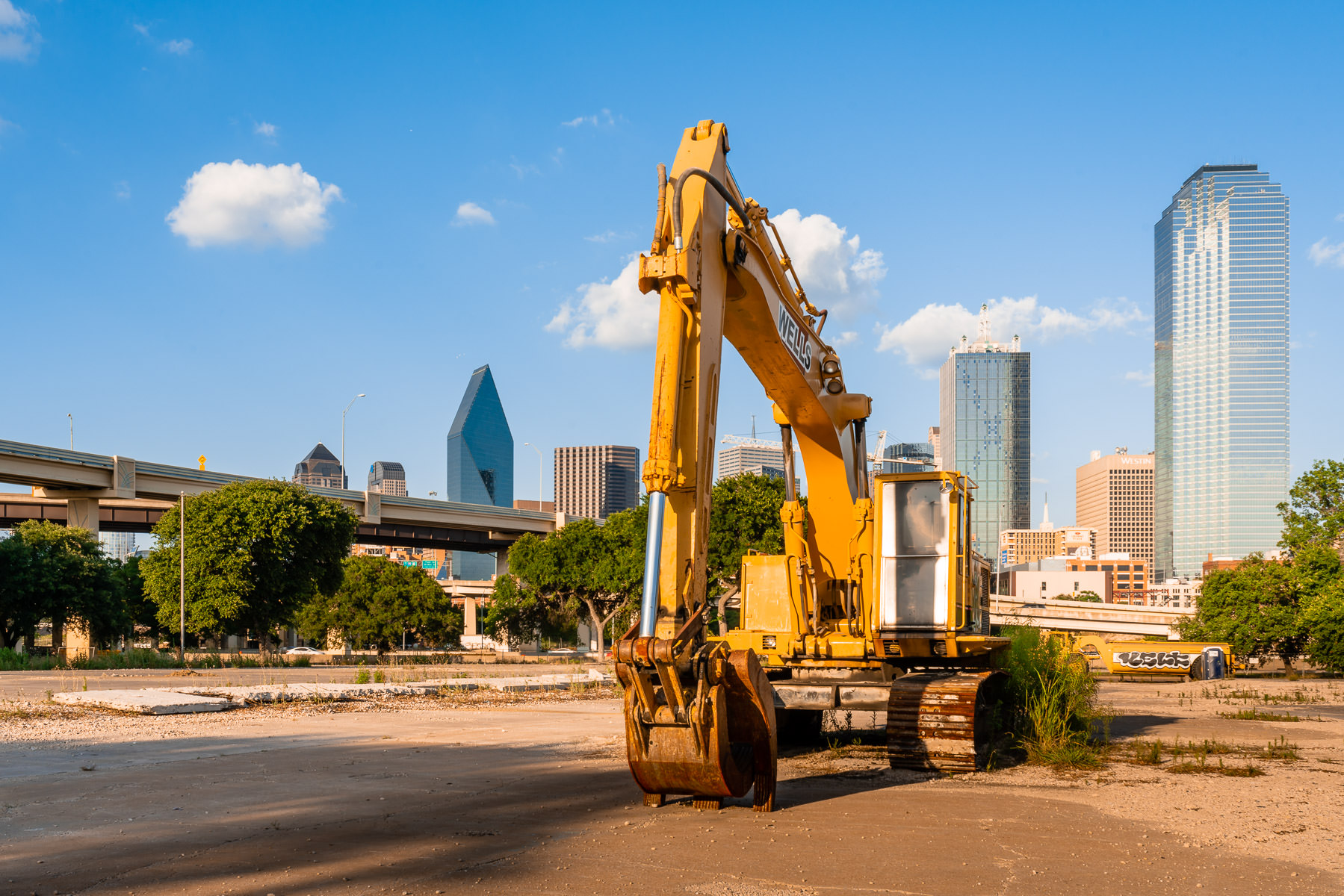 A backhoe sits idle in a vacant lot near Downtown Dallas.