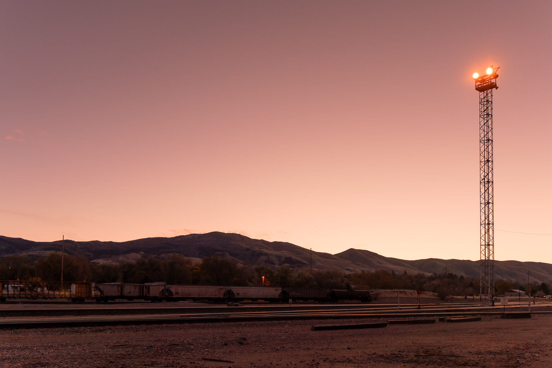 A light tower oversees a rail yard on the outskirts of Pocatello, Idaho, as the sun rises on the surrounding hills.
