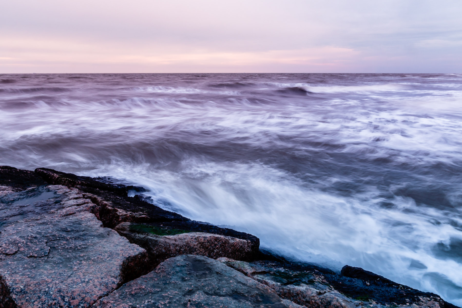 The waves of the Gulf of Mexico are smoothed by a long exposure as the sun begins to rise on the Galveston, Texas, beach.