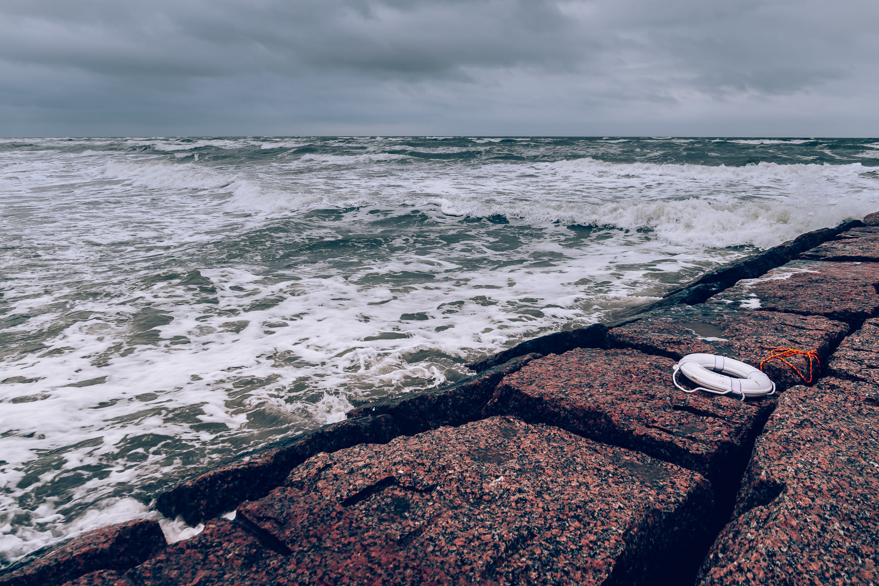 A life preserver lies abandoned on a granite jetty along the Gulf Coast shore in Galveston, Texas.