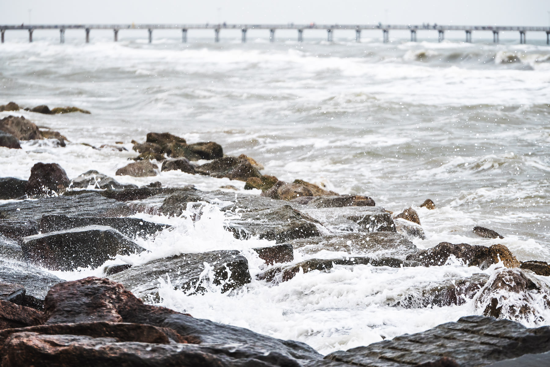 Surf crashes onto granite blocks along the seawall in Galveston, Texas.