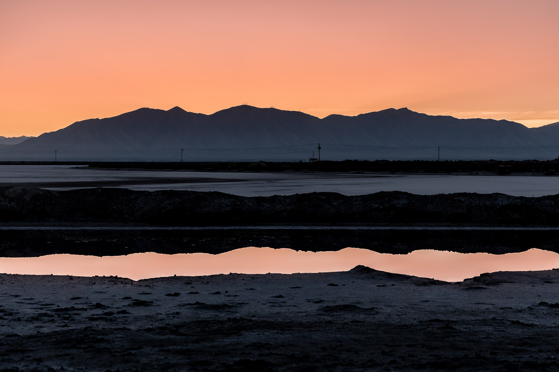 The first light of the morning sun reflects in the still waters of a roadside wash near the Great Salt Lake's Stansbury Island, Utah.