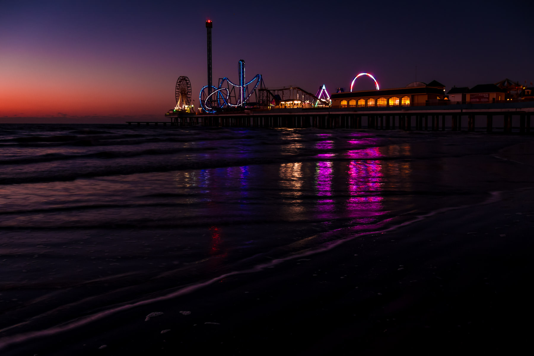 The first light of day rises on the Gulf of Mexico as the lights from Galveston, Texas' Historic Pleasure Pier reflect on the surf.