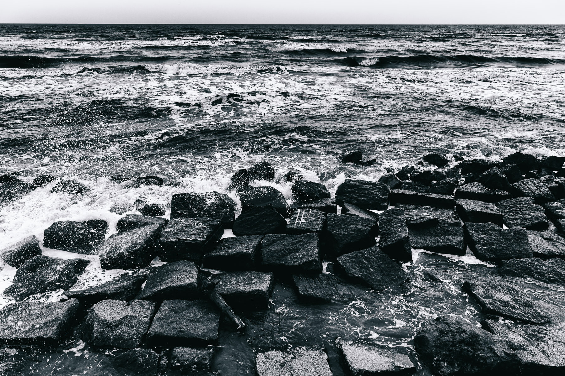 The Gulf of Mexico surf crashes over granite blocks along the seawall in Galveston, Texas.