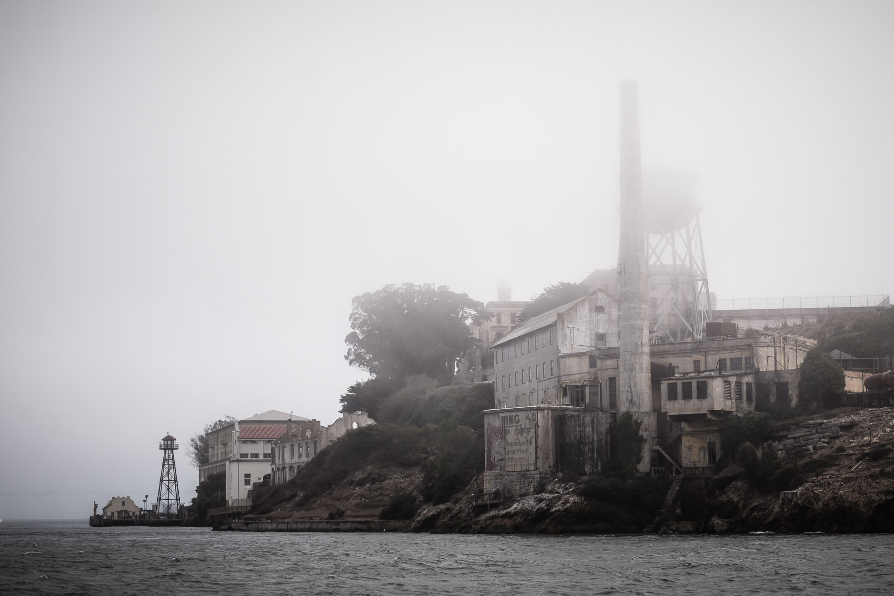 The historic Alcatraz Island sits in San Francisco Bay, partially shrouded by the fog.