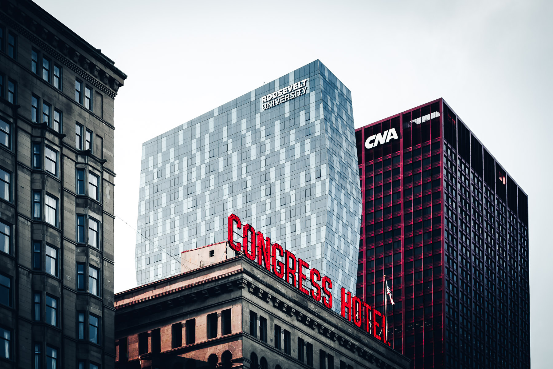 The neon sign of Chicago's Congress Hotel, overshadowed by surrounding skyscrapers.