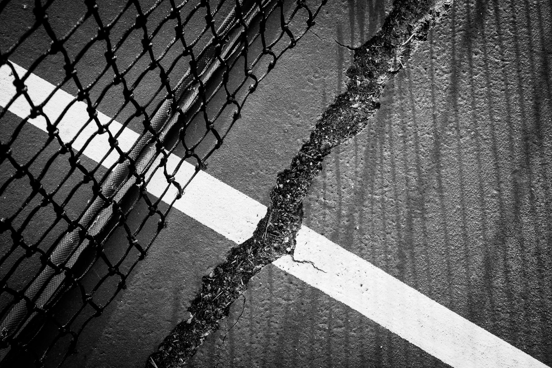 A crack in a tennis court at Tyler, Texas' Pollard Park.