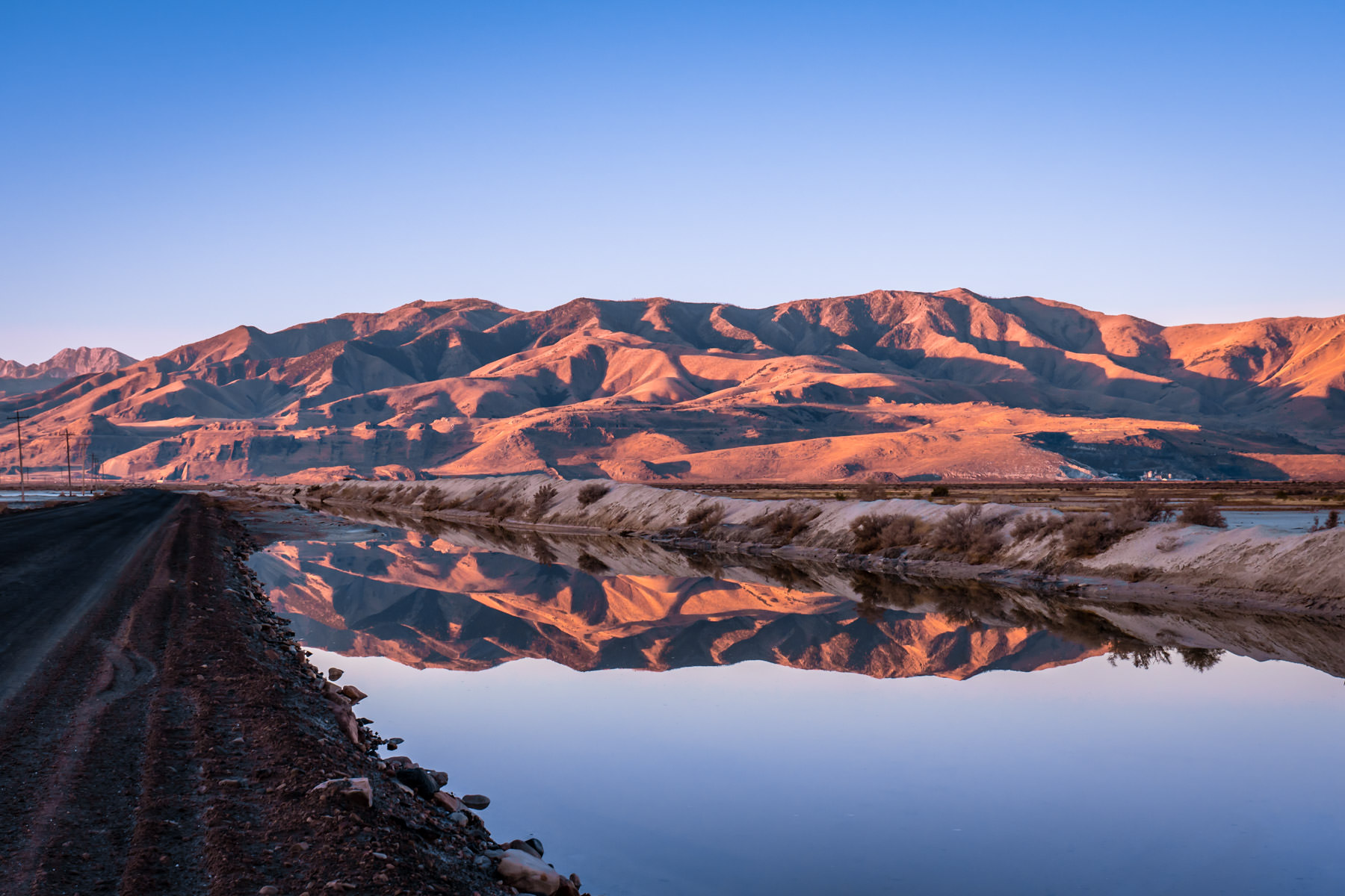 Mountains near Utah's Stansbury Island reflect in a still roadside pond.