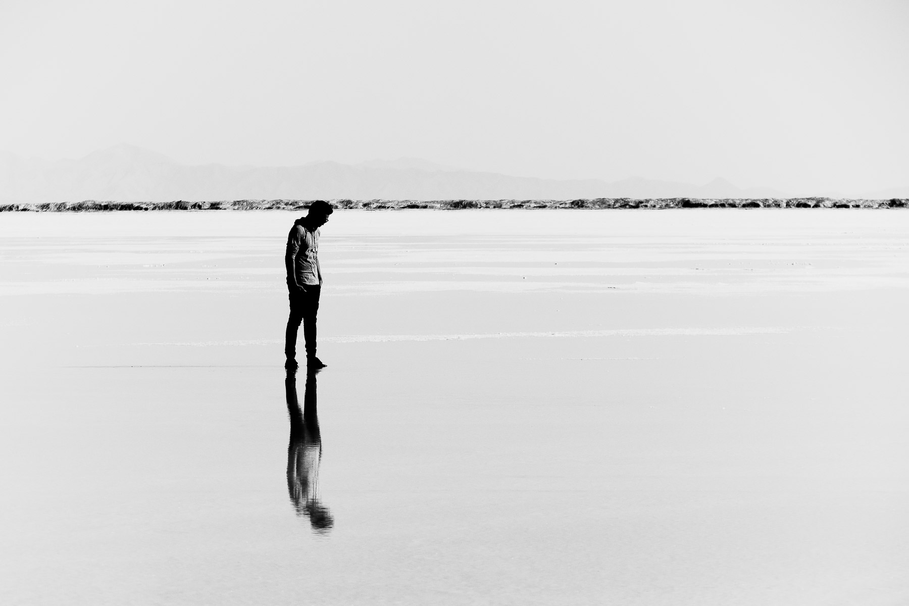 A visitor to Utah's Bonneville Salt Flats is reflected in a sheen of water atop the barren plain.