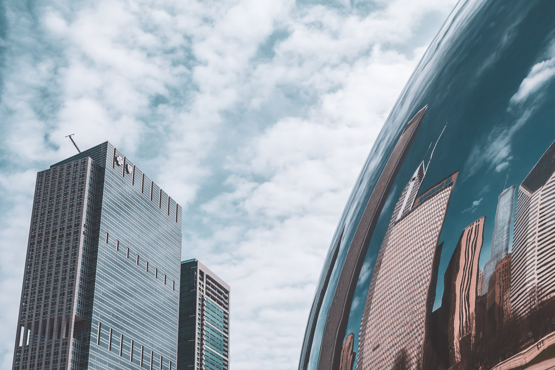 """Chicago's Blue Cross-Blue Shield Tower and 340 on the Park rise above Anish Kapoor'sCloud Gate, colloquially known as """"The Bean""""."""